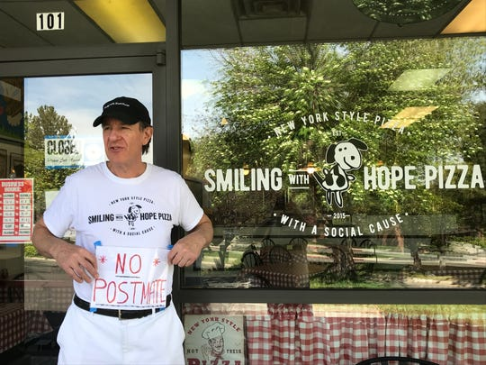 "Walter Gloshinski, co-owner of nationally recognized Smiling with Hope Pizza of Reno, holds the ""No Postmate"" sign usually displayed in the restaurant's window. He didn't want to participate with the Postmates delivery service; it took dozens of requests to have the pizzeria removed from the app."