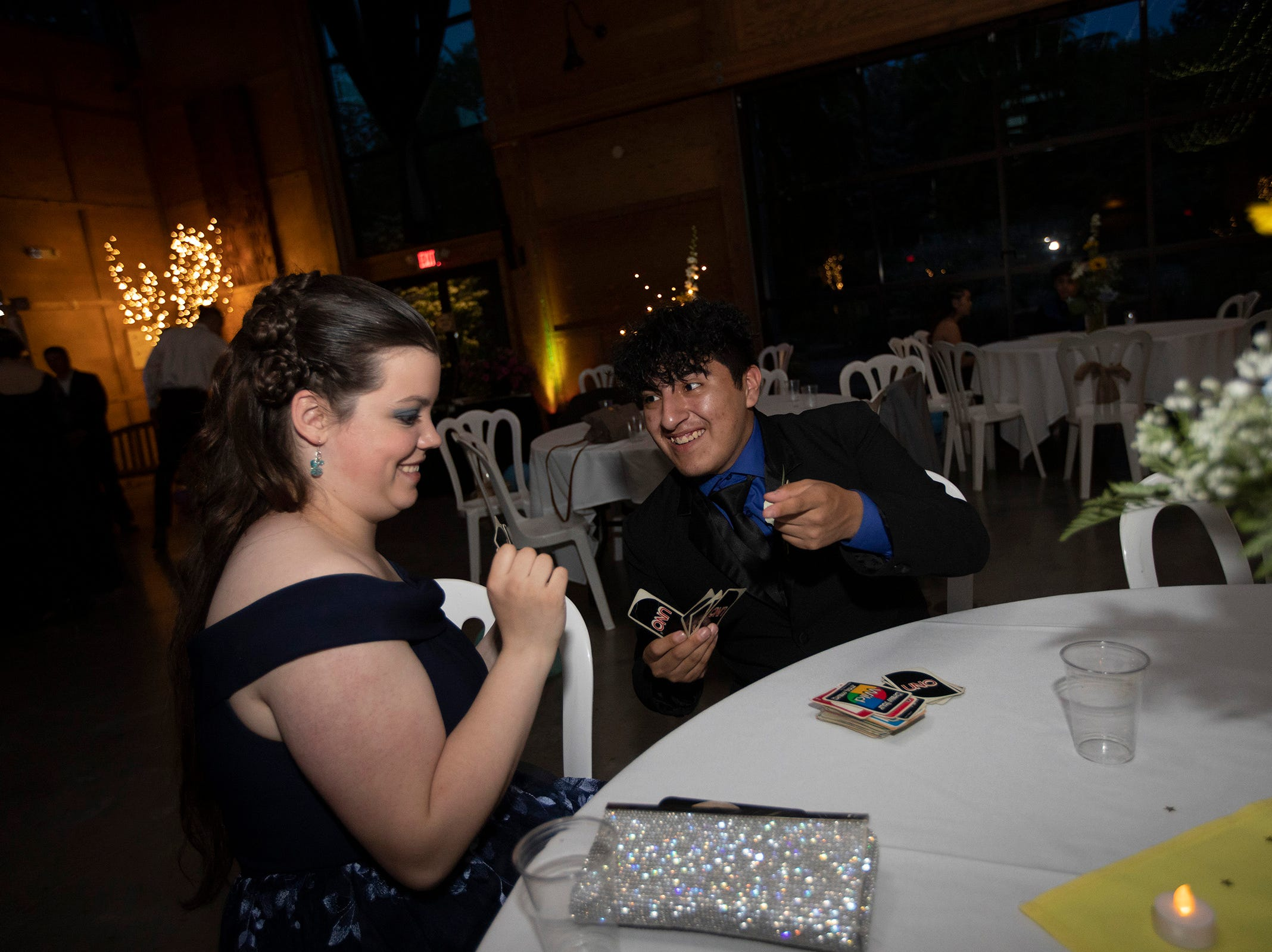 Olivia Patterson, 18, and Marco Garcia, 18, play uno during the Silverton High Schoo prom at the Oregon Garden on Saturday, May 11.