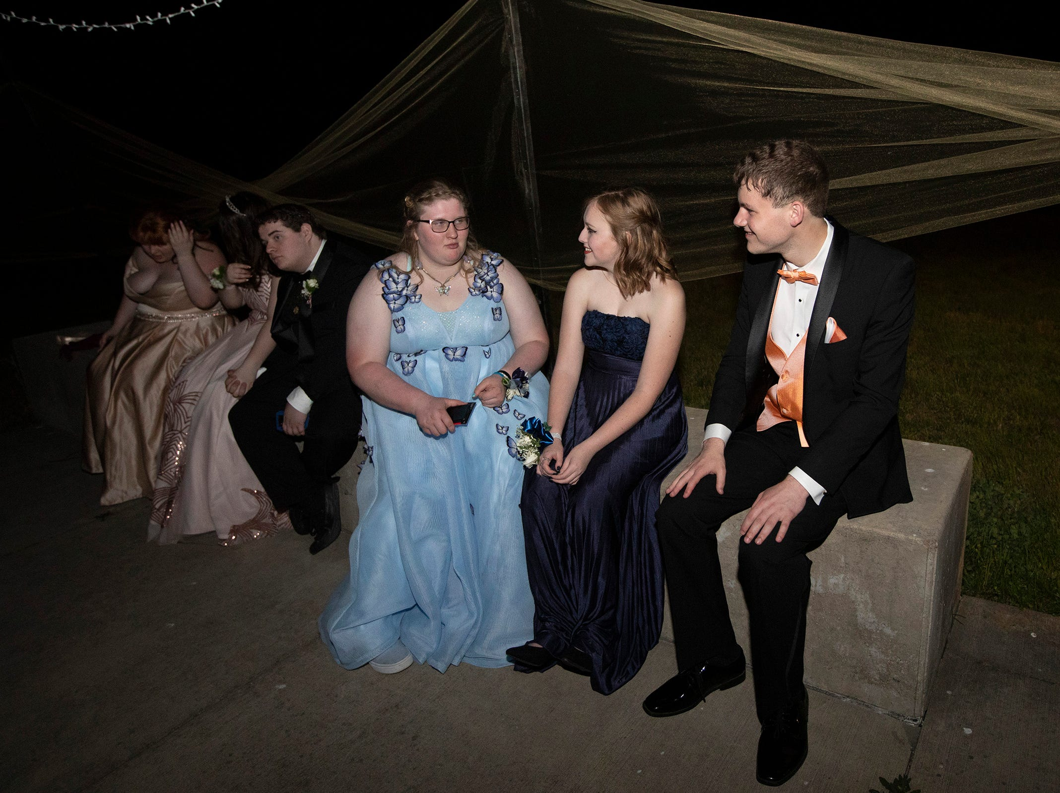 Gillian Ross, Kaitlin Anderson and Zachary Ludwig take a break from dancing to sit on the patio during the Dallas High School prom at the Dallas Armory on Saturday, May 12.