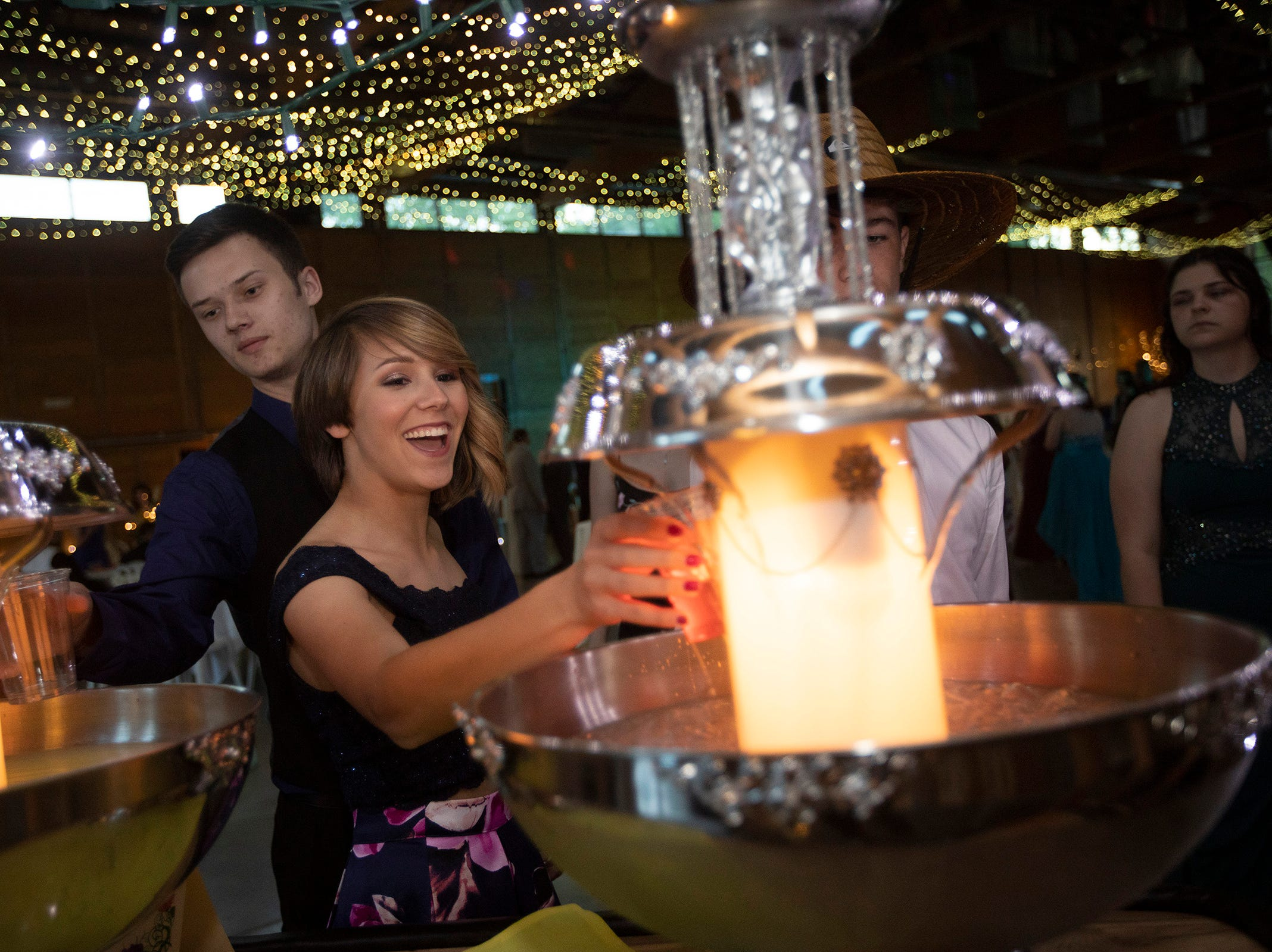 Ayva Bradford, 16, fills a glass of punch during the Silverton High School prom at the Oregon Garden on Saturday, May 11.