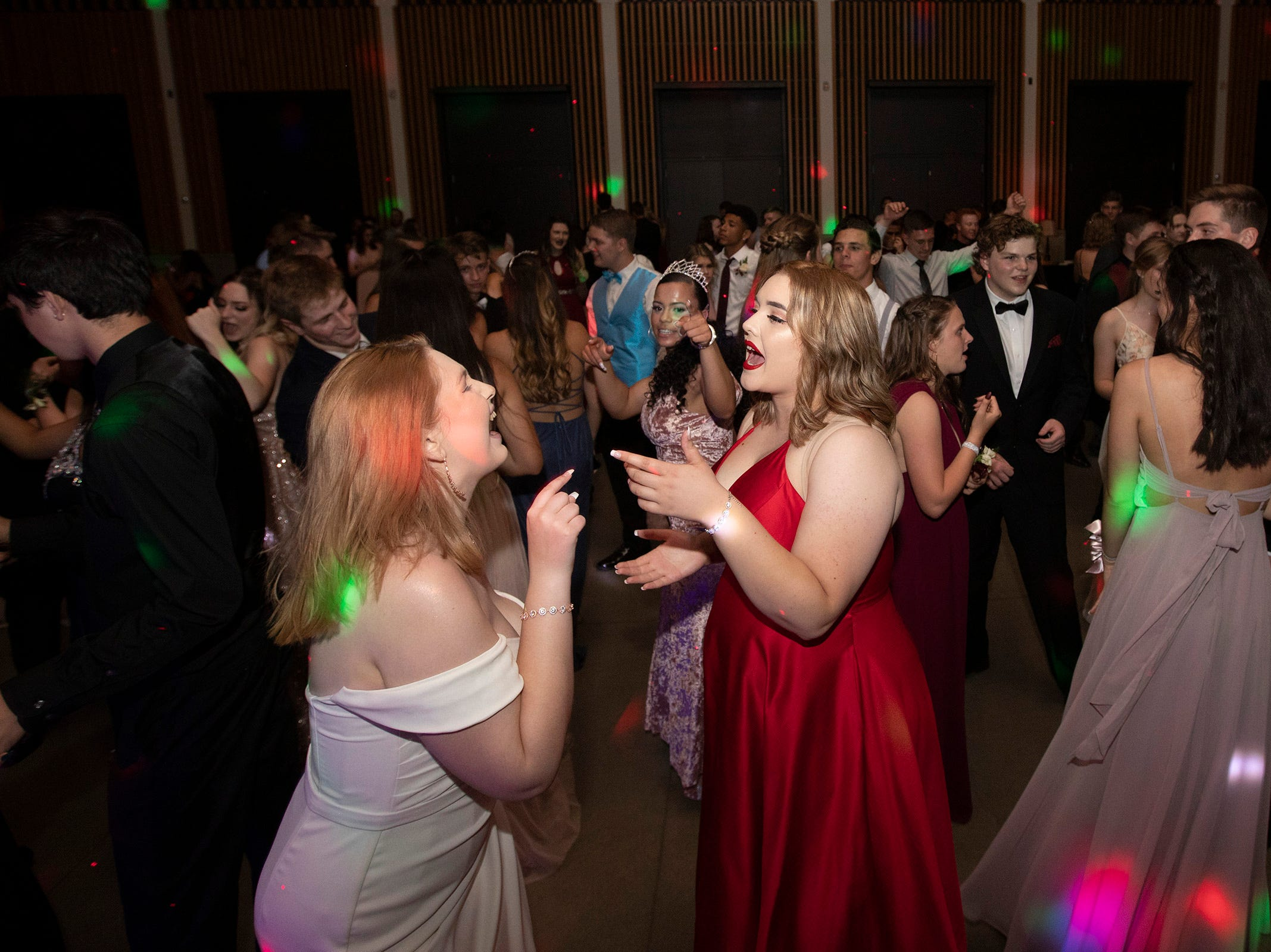 Taylor Snoha, left, and Samantha Urrutia sing along while dancing during the Dallas High School prom at the Dallas Armory on Saturday, May 12.
