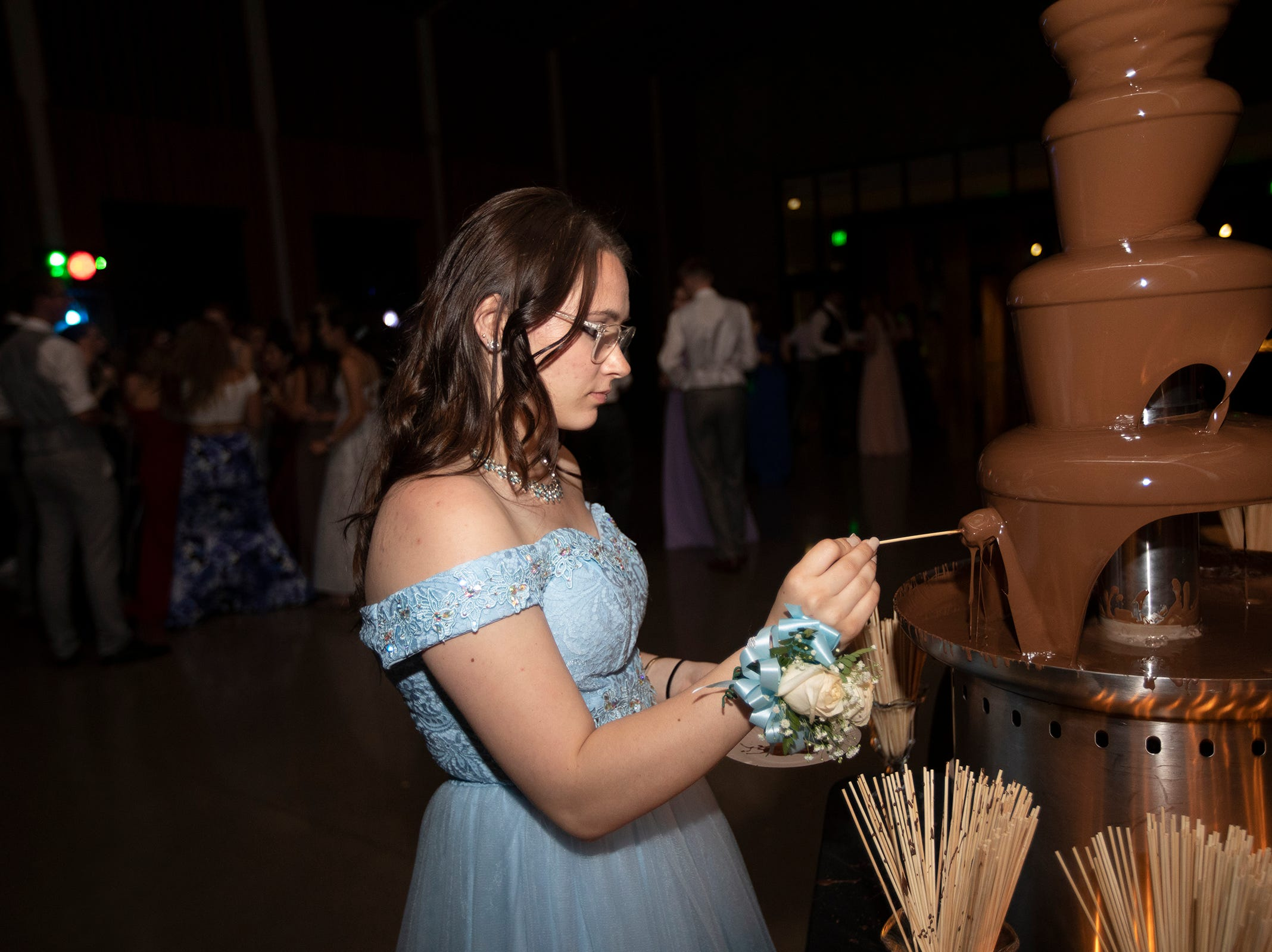 Jenna King dips a marshmellow in the chocolate fountain during the Dallas High School prom at the Dallas Armory on Saturday, May 12.