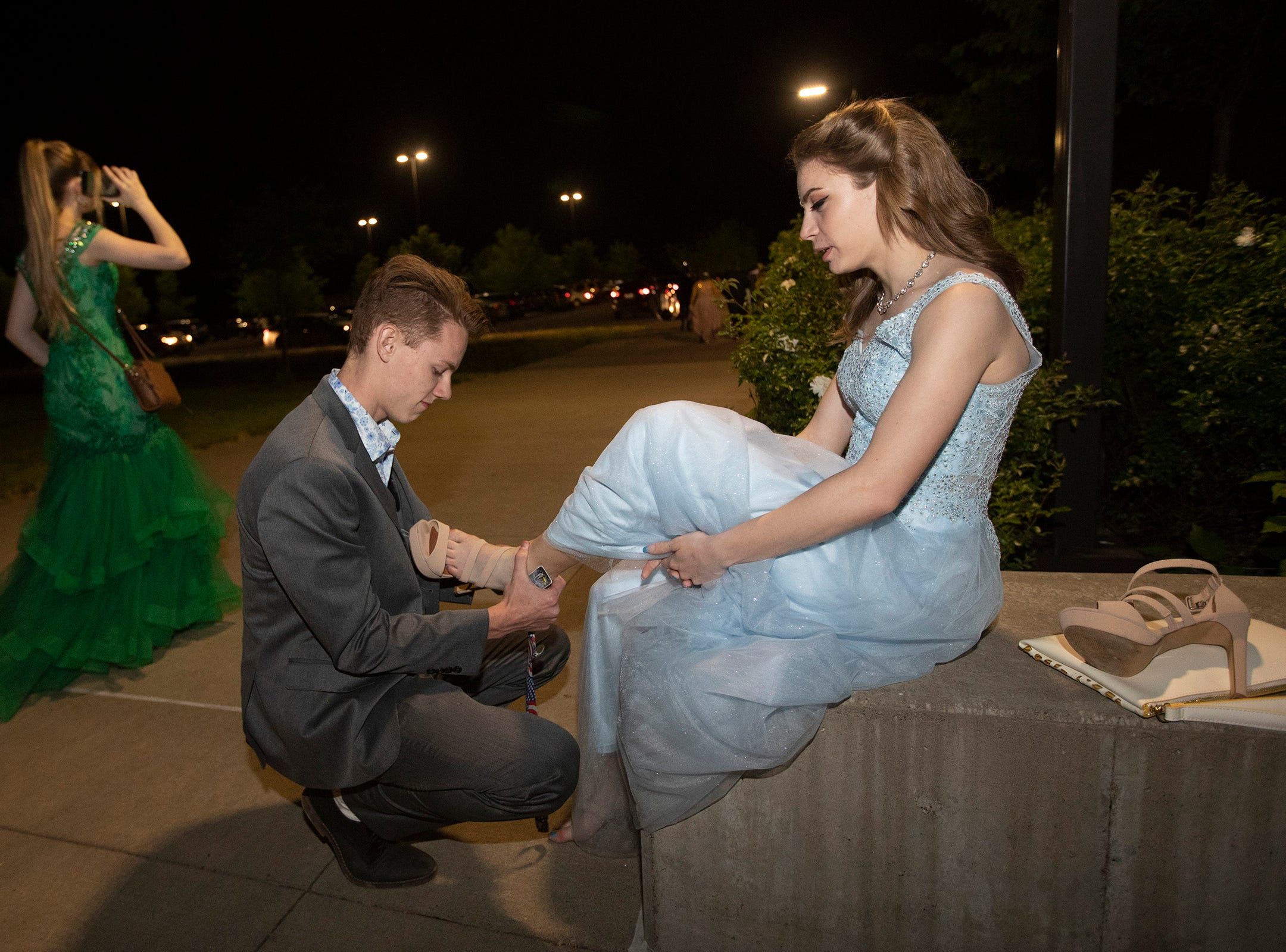Preston Mack helps Melody Height with her shoe following the Dallas High School prom at the Dallas Armory on Saturday, May 12.