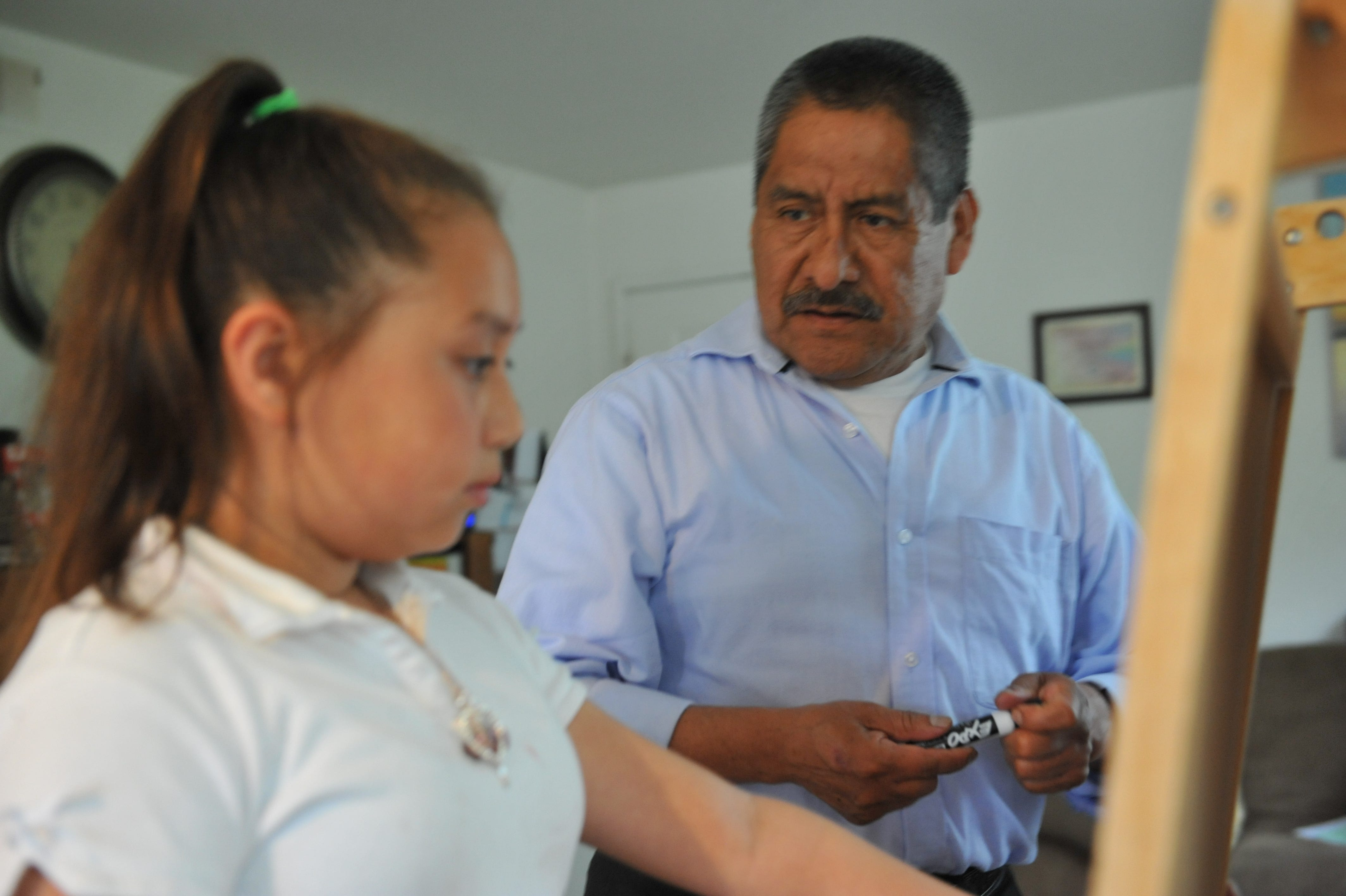 Adolfo González helps his granddaughter Kayla with her homework using the whiteboard in his Salinas home.