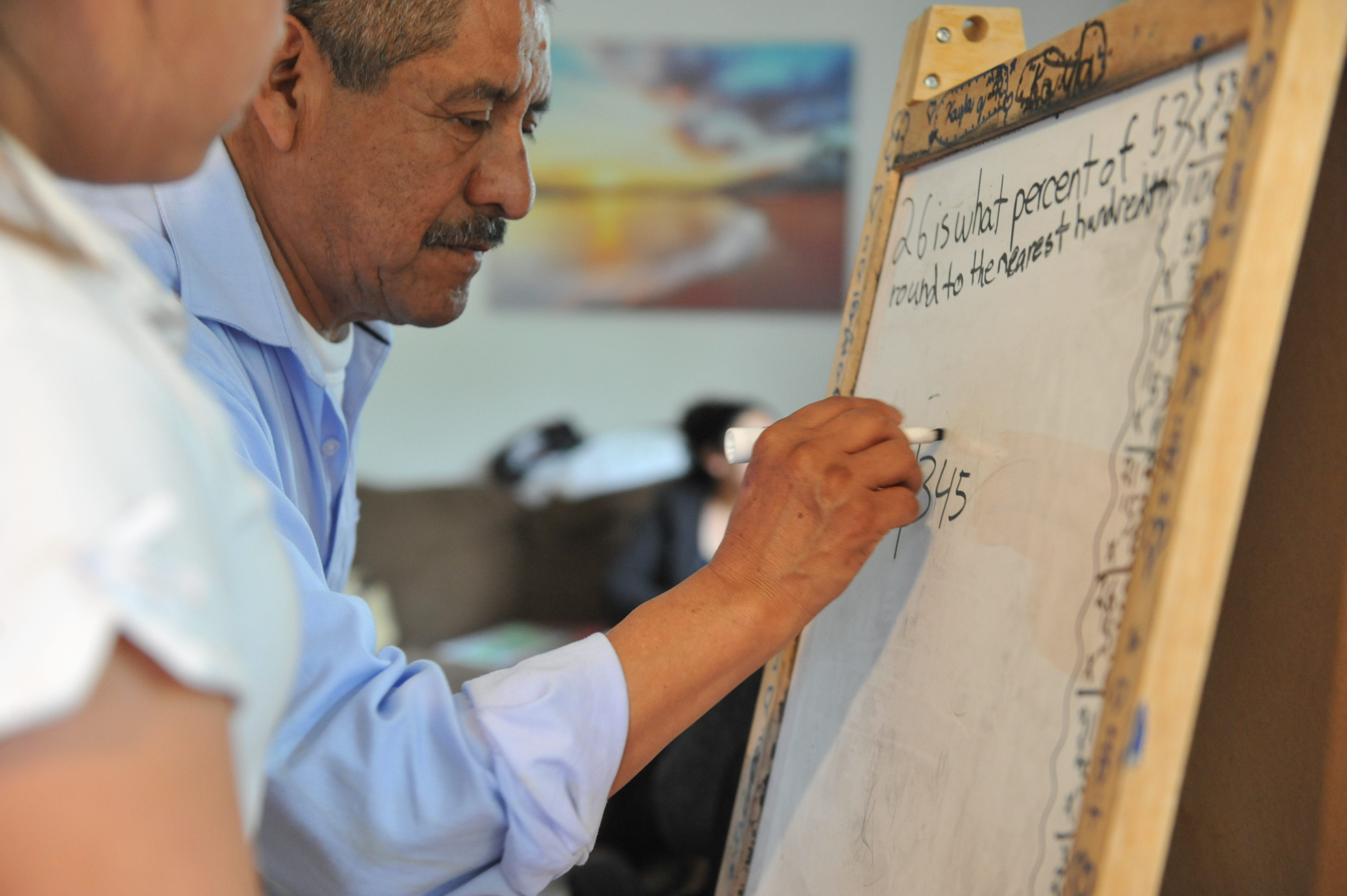 Adolfo González helps his granddaughter Kayla with her homework at his Salinas apartment.