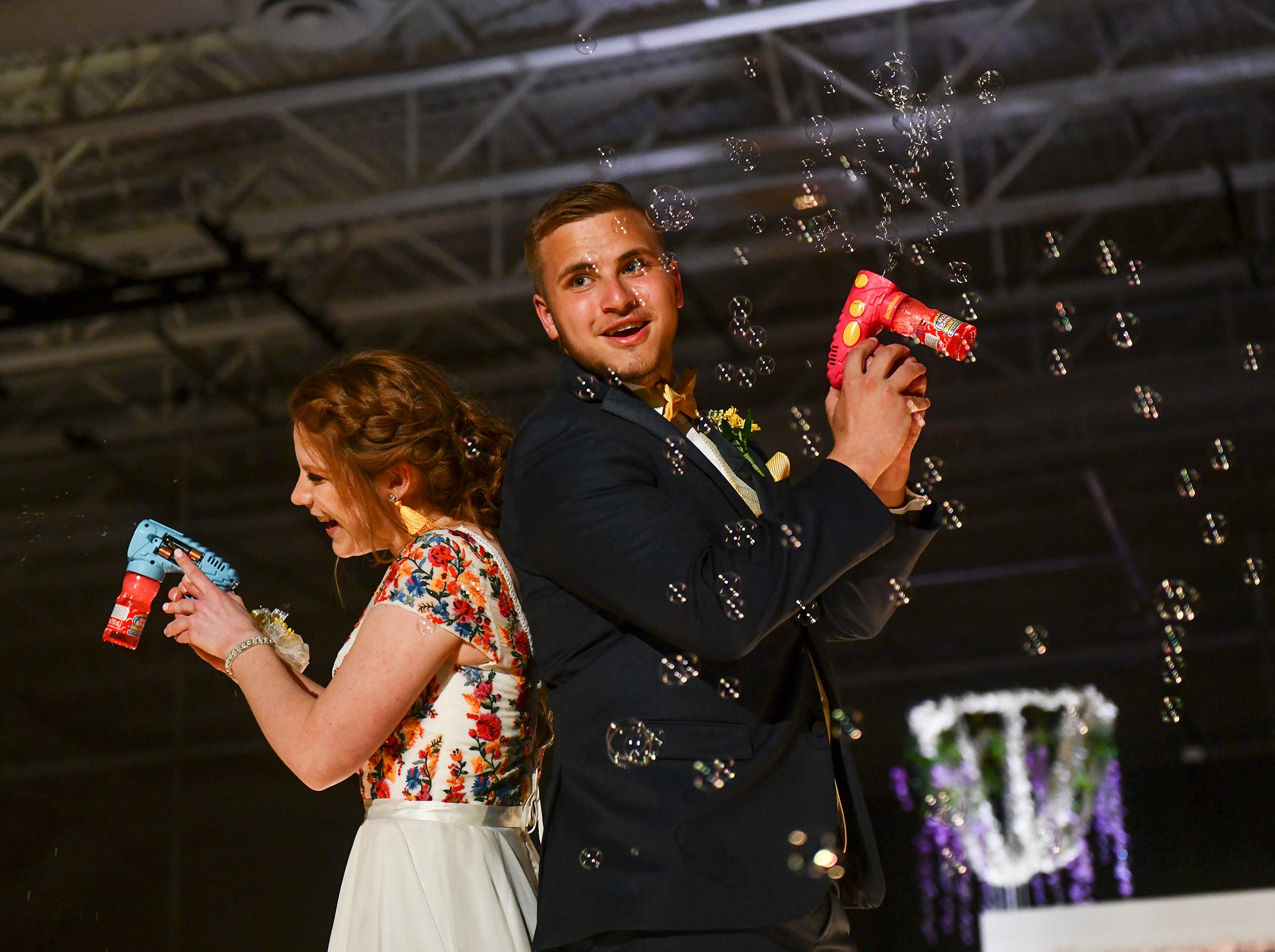 Bubble guns serve as a prop for a couple during prom grand march Saturday, May 11, at Sauk Rapids-Rice High School.