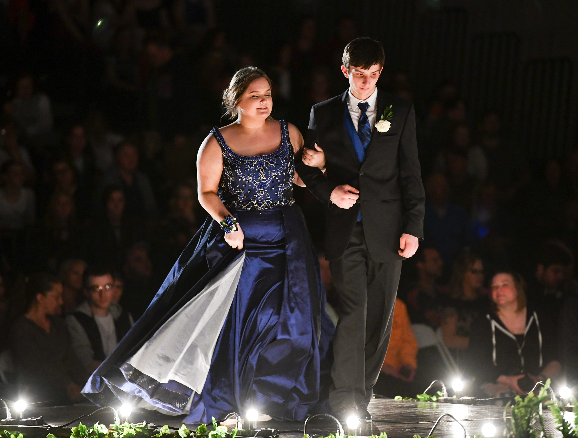 A couple takes their turn at prom grand march.