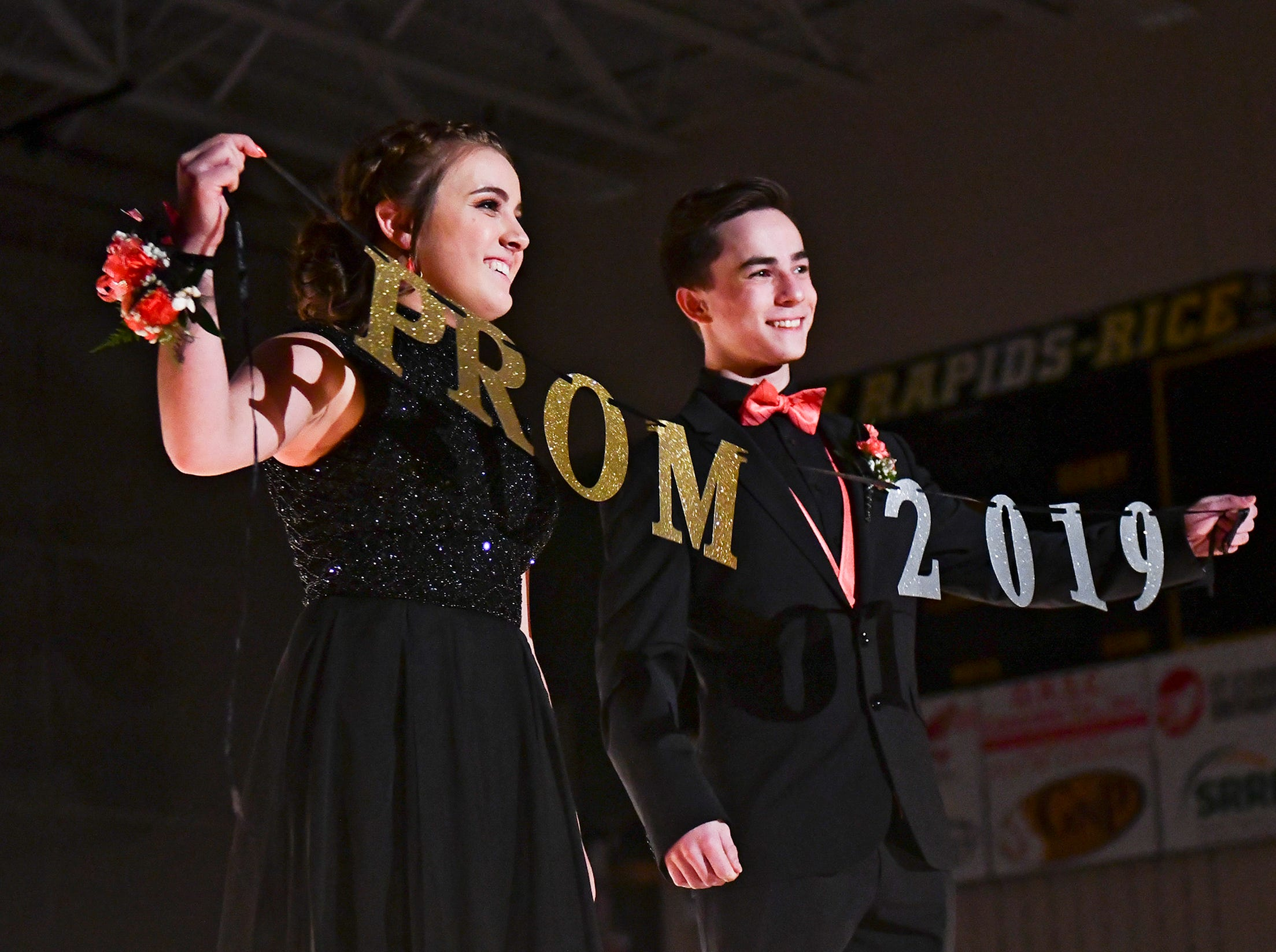 A couple holds a sign during their turn at prom grand march Saturday, May 11, at Sauk Rapids-Rice High School.
