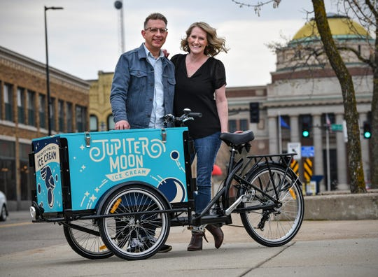 Co-owners and founders David Boyer and Megan Freas stand next to the Jupiter Moon Ice Cream cycle Saturday, May 11, in St. Cloud.
