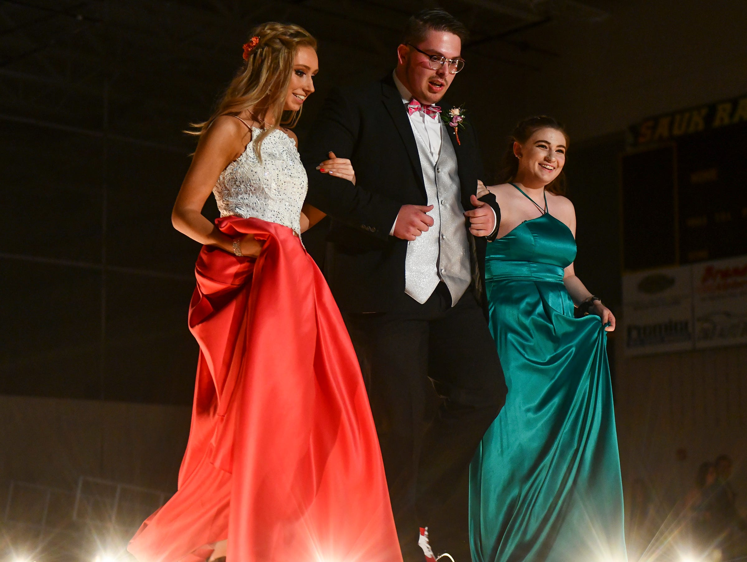 Friends join arms during their turn at prom grand march Saturday, May 11, at Sauk Rapids-Rice High School.