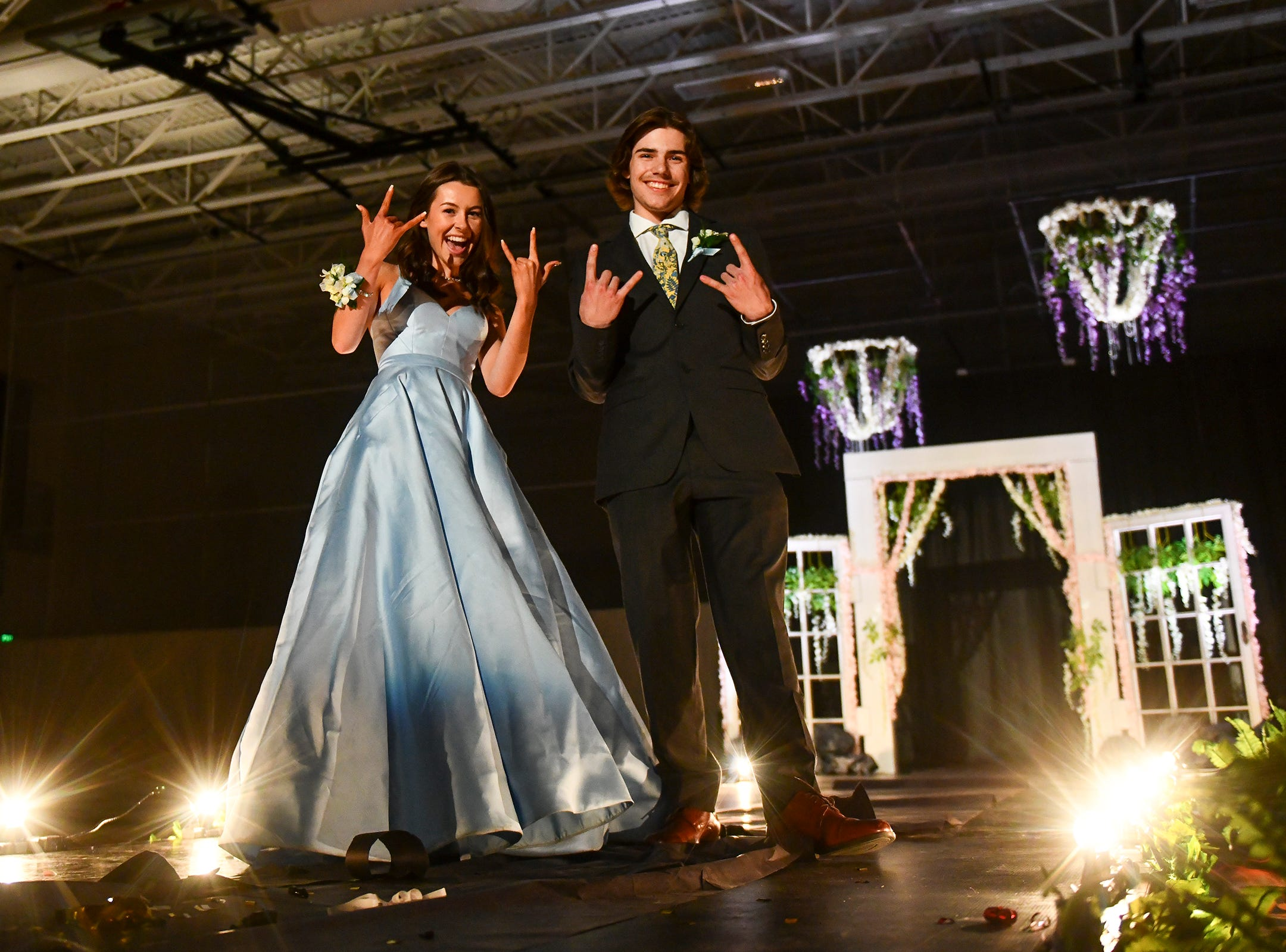 A couple strikes a pose during their turn at prom grand march.