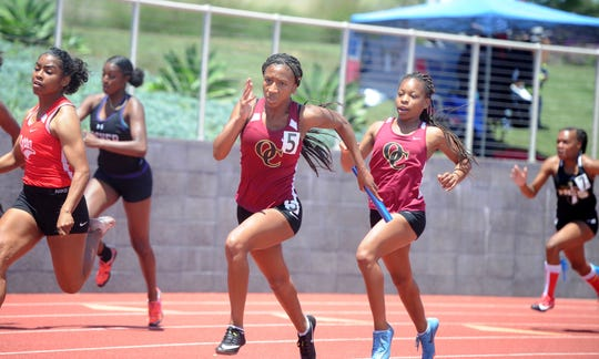 Oaks Christian's Jahzara Richardson receives the baton from a teammate during the Division 4 4x100 relay at the CIF-SS Track and Field Championships at El Camino College in Torrance on Saturday. Oaks Christian won the 4x100 title in 3:48.73 and captured the overall girls and boys team titles for the division.