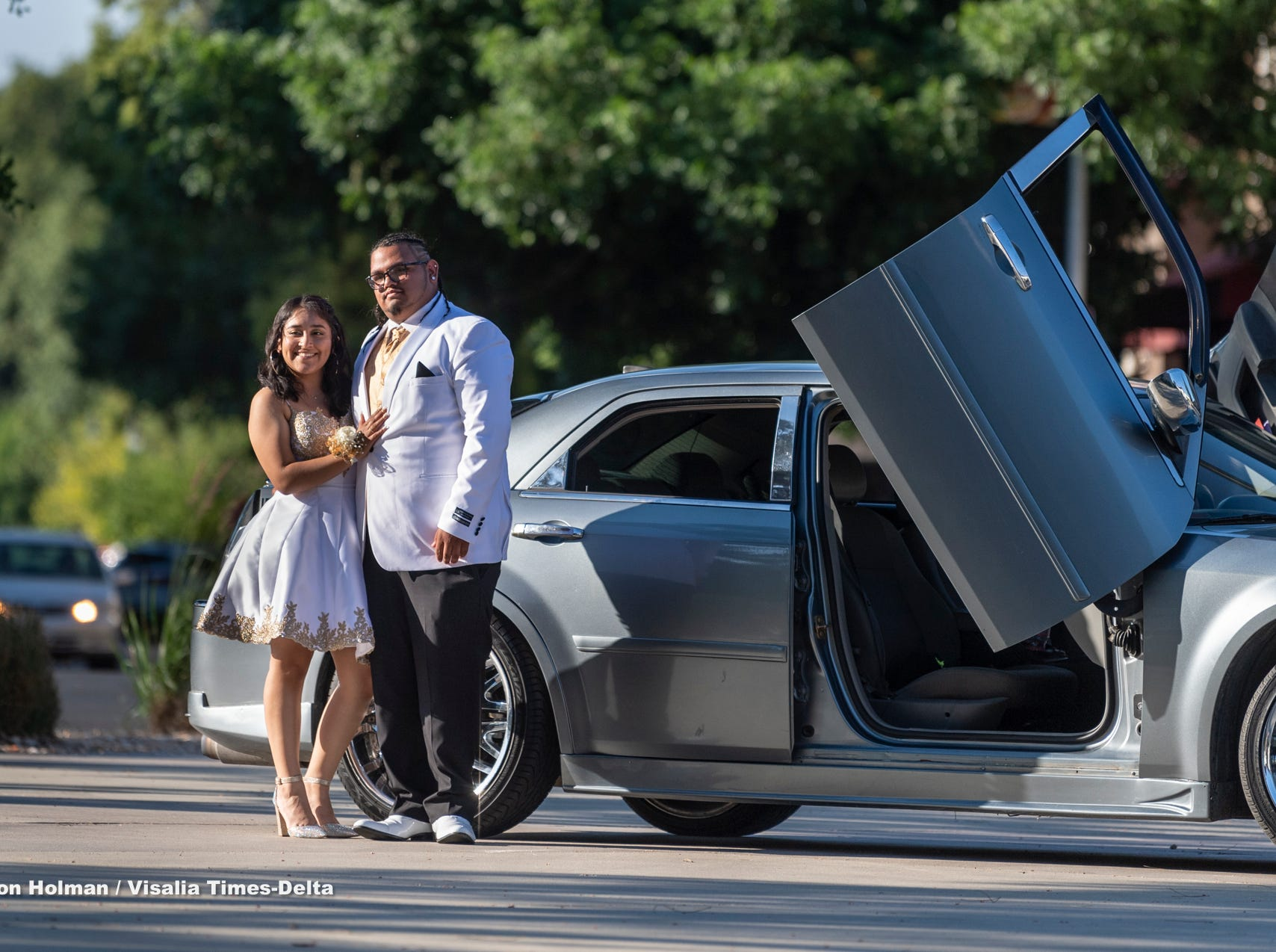 El Diamante student Isaac Magallon, right, and his date Ofie Zuniga step out from a customized Chrysler 300 for Visalia Unified School District's High School prom on Saturday, May 11, 2019.