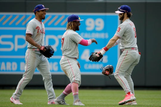 Philadelphia Phillies outfielders Nick Williams, left, Odubel Herrera, center, and Bryce Harper (3) celebrate after their baseball game against the Kansas City Royals, Sunday, May 12, 2019, in Kansas City, Mo.