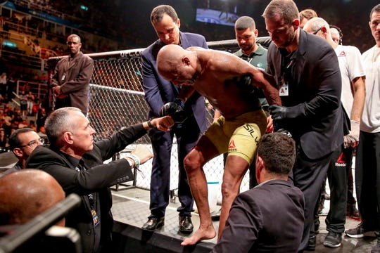 Anderson Silva is helped out of the ring after suffering an apparent knee injury against Jared Cannonier.