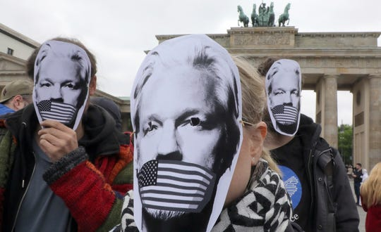 People wear paper masks to protest against a possible extradition of WikiLeaks founder Julian Assange to the USA in front of the Brandenburg Gate in Berlin, Germany, May 2, 2019.