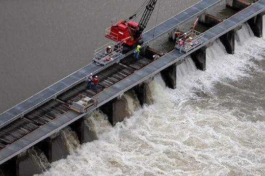 Workers open bays of the Bonnet Carre Spillway, to divert rising water from the Mississippi River to Lake Pontchartrain, upriver from New Orleans, in Norco, La., Friday, May 10, 2019. Torrential rains in Louisiana brought such a rapid rise on the river that the Army Corps of Engineers is opening the major spillway four days earlier than planned. Spokesman Ricky Boyett says the river rose six inches in 24 hours, with more rain expected through the weekend. (AP Photo/Gerald Herbert) ORG XMIT: LAGH103