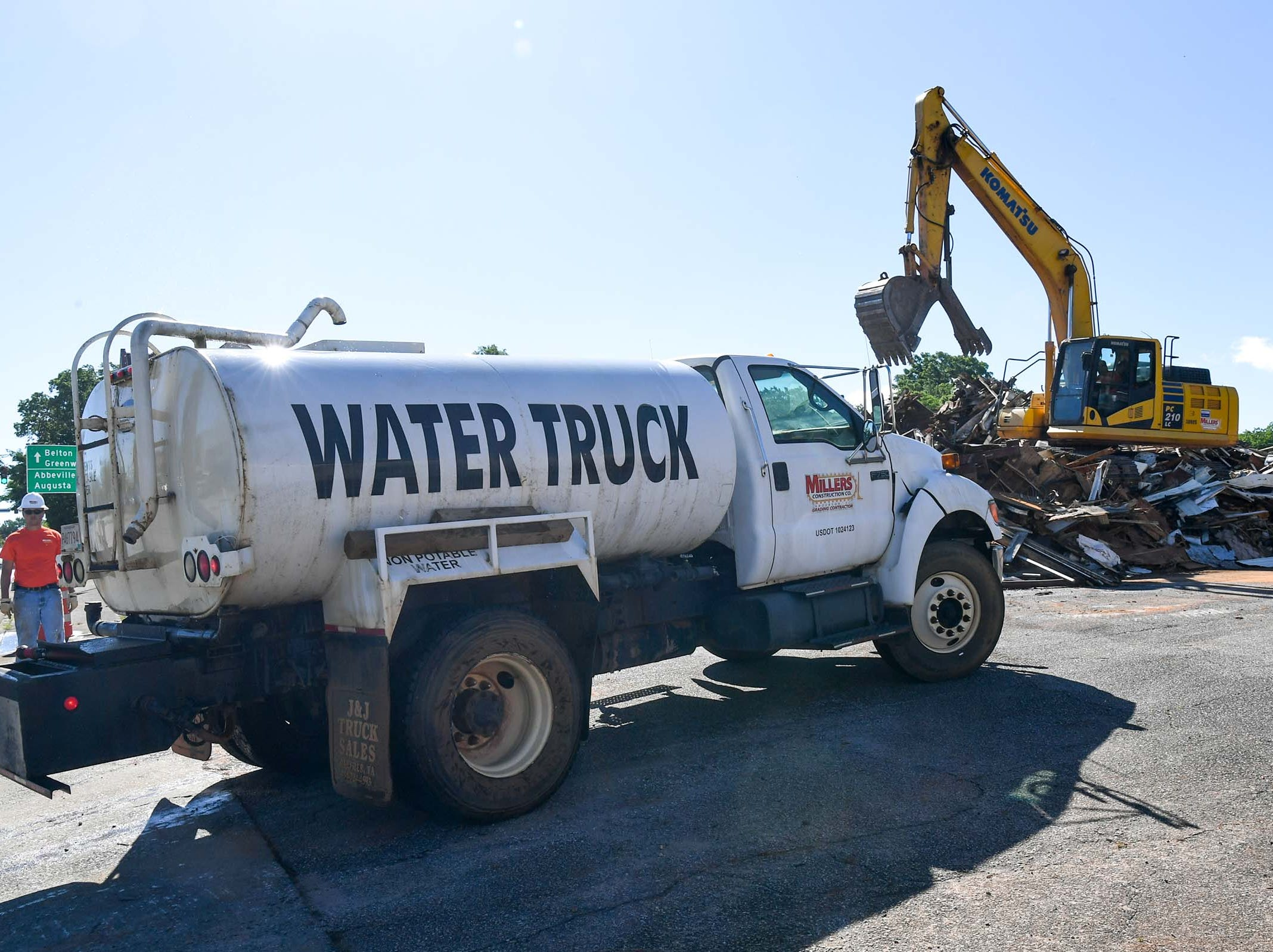 A water truck from Miller Construction of Anderson arrives while an excavator gets ready to load a dump truck with debris during demolition of the 600 South Main Street building Monday in Anderson. The building was used as a city planning and codes for years after McDougalds Funeral Home occupied it from 1934 to 1968 as their South Chapel.