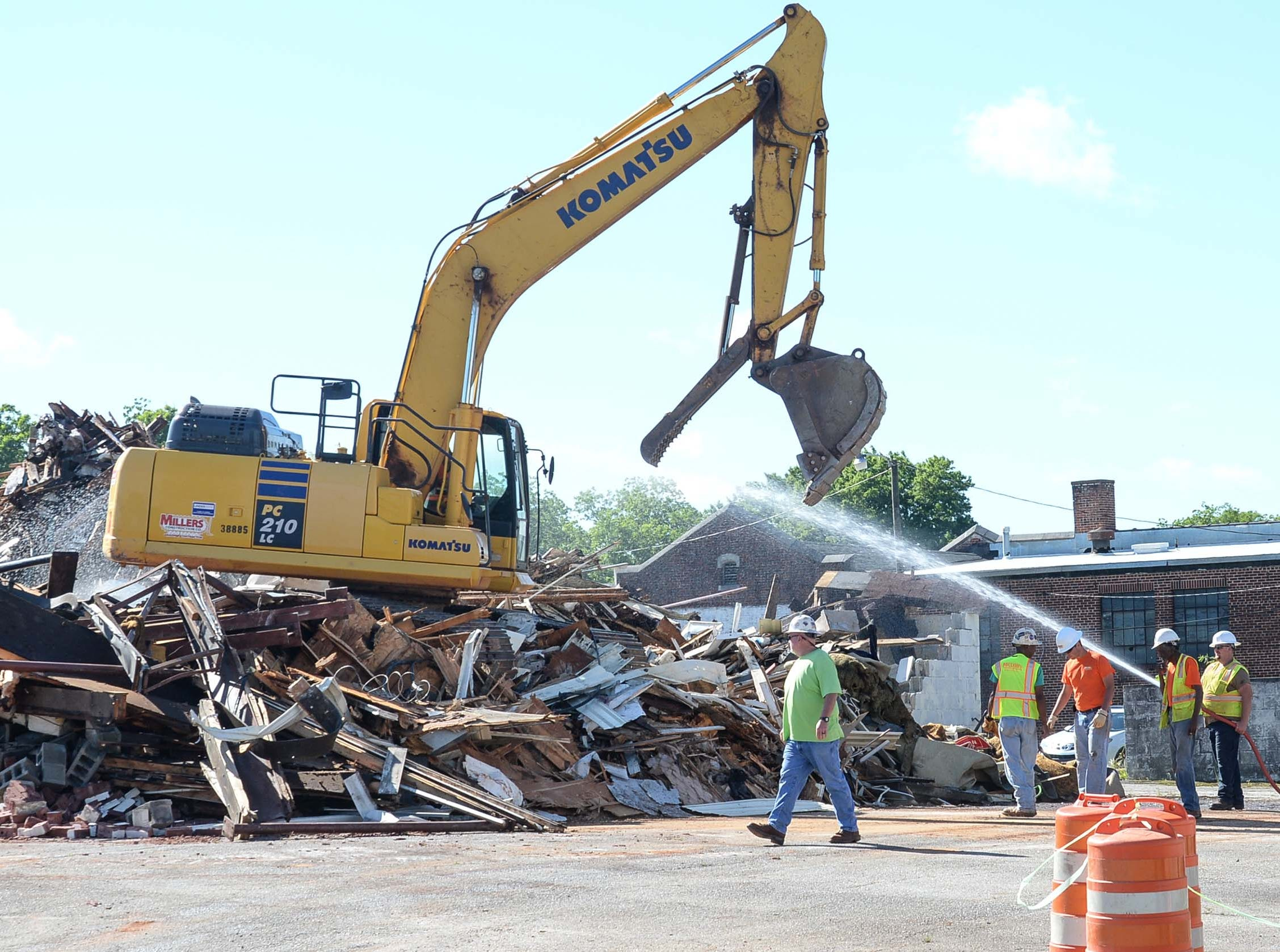 A worker from Miller Construction of Anderson sprays down dust from debris during demolition of the 600 South Main Street building Monday in Anderson. The building was used as a city planning and codes for years after McDougalds Funeral Home occupied it from 1934 to 1968 as their South Chapel.