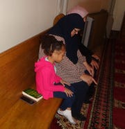 Nova Pauling-Payne, 4, left, and her grandmother, Mary Afifi, pray at the Islamic Awareness Center in Binghamton. The center is one of 23 houses of worship that people can visit during the Sacred Sites Open House Sunday tour on May 19.