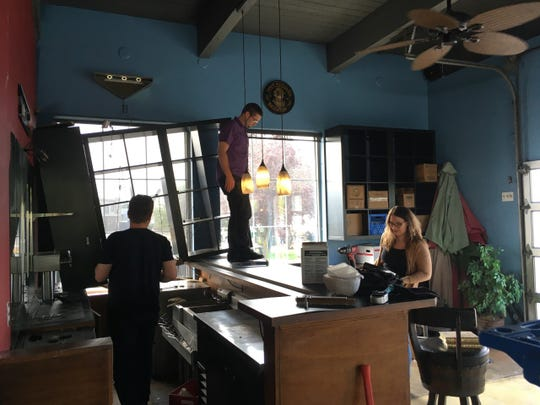 Blake Ecklund, left, Cody Morgan, center and Samantha Wells, right work to ready the old Amy's on the Bay space for Peninsula BevCo.