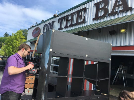 Cody Morgan, co-owner of Peninsula BevCo, takes apart a cabinet at the former Amy's on the Bay restaurant in Port Orchard. Peninsula BevCo is renovating the leased space and will move permanently in July.