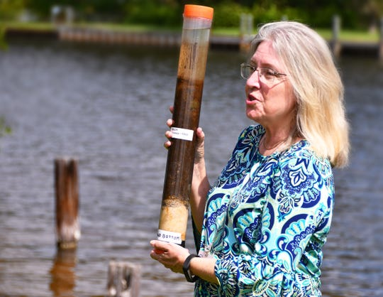 Ann Shortelle, executive director of the St. Johns River Water management District, holds up a core sample of the river bottom. A celebration was held at Ballard Park Monday morning with representatives from St. Johns River Water Management District, Florida Department of Environmental Protection, elected officials and Indian River Lagoon advocates for the completion of the muck dredging project.
