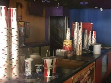 Empty paper cups are stacked on the counter inside the Satellite Cinemas on Sunday.