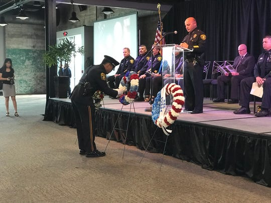 An officer places a flower on a wreath to honor a fallen officer during the 13th annual Coastal Bend Regional Peace Officers Memorial Day Ceremony.