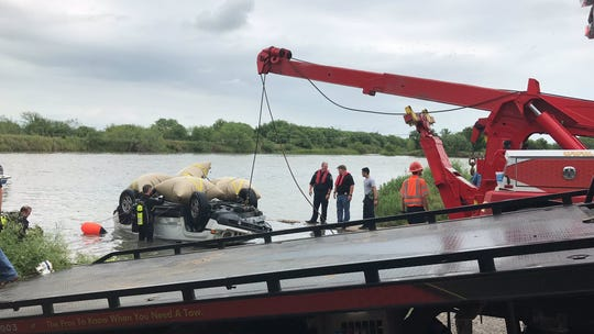 Corpus Christi Dive Team officers and Apollo Towing Service crews get a white Jeep Patriot out of the Nueces River near Labonte Park on Monday, May 13, 2019.