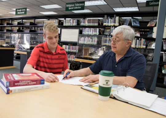 Cody Clark, left, helps tutor college students like Mike Henry, a Human Services Technology major, in subjects like algebra.