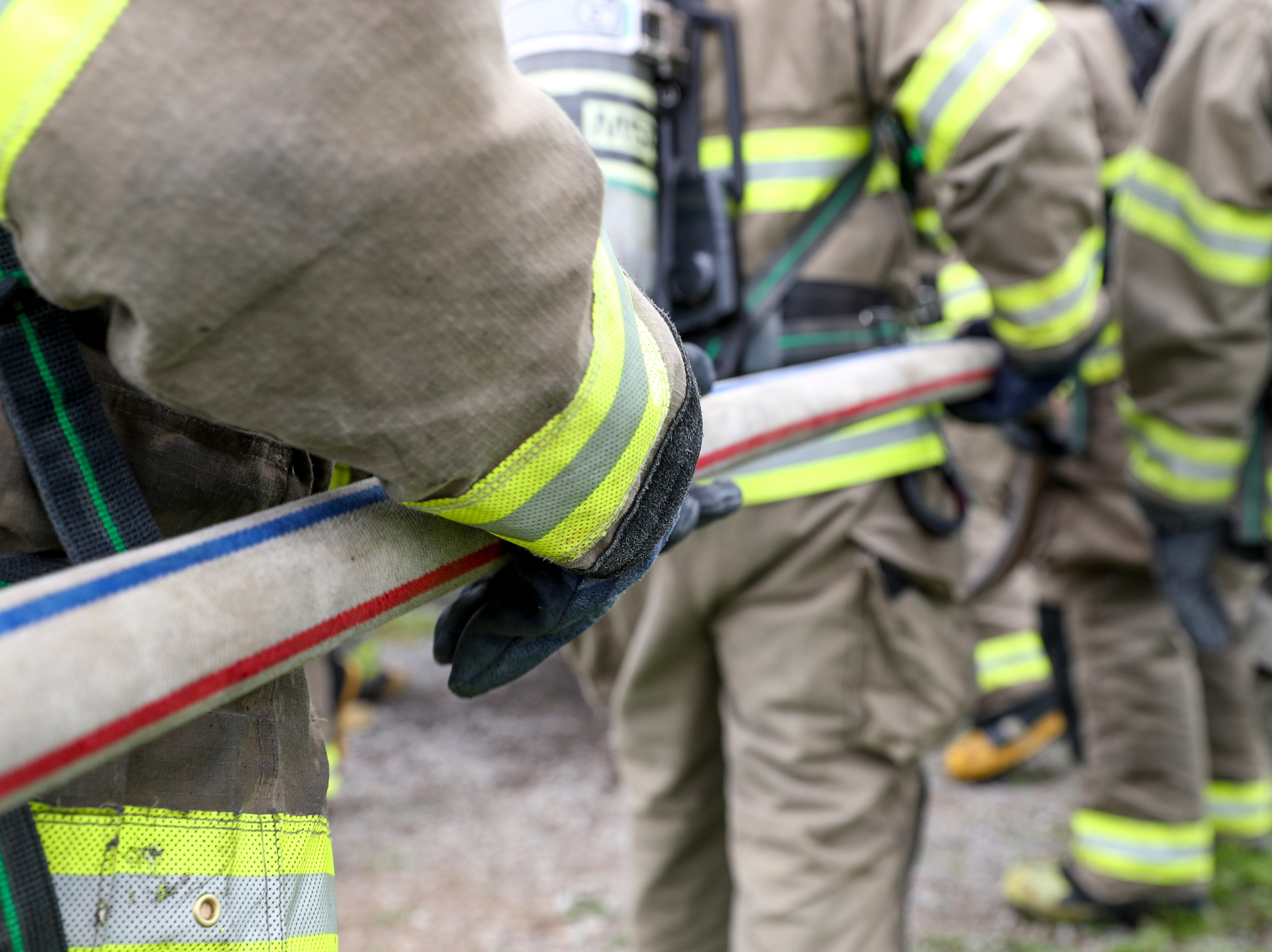 New recruits help control and guide a hose into the burn building at Clarksville Fire Rescue in Clarksville, Tenn., on Friday, May 10, 2019.
