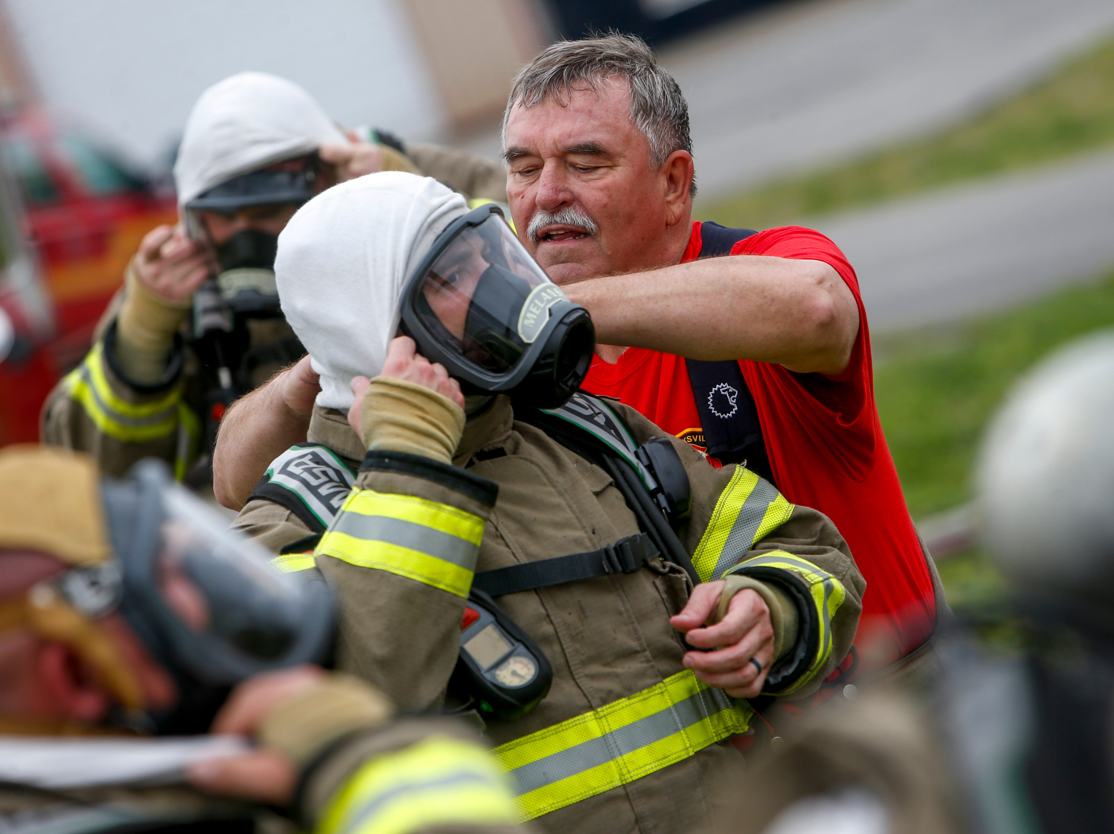 Chief Mike Roberts helps Bobby Melanson remove his mask during a live fire drill at Clarksville Fire Rescue on Friday, May 10, 2019. After 42 years with the department, Roberts will retire effective July 31.