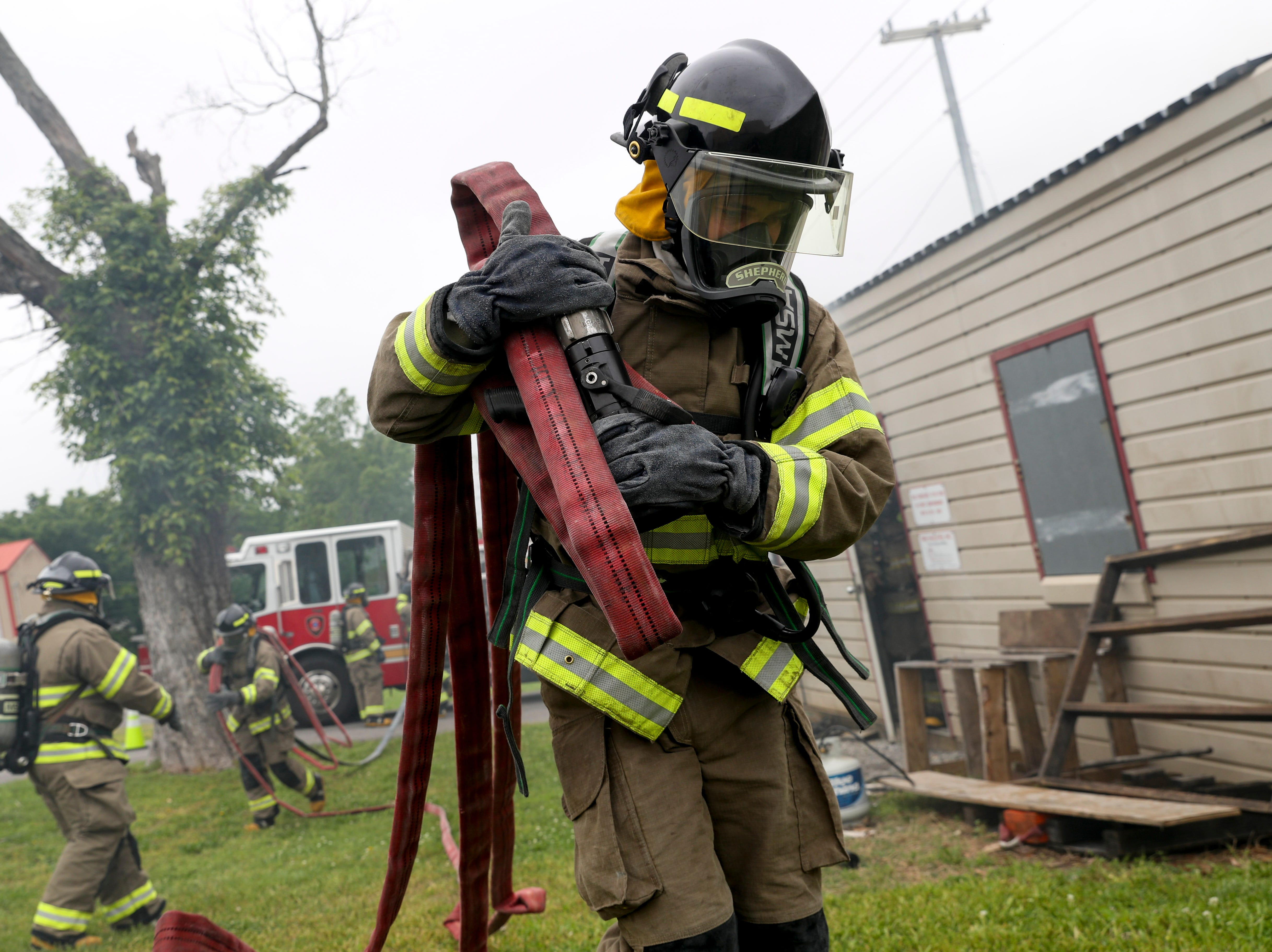 Chayce Shepherd walks with a hose hoisted over his shoulder, spreading it for use at a live fire drill at Clarksville Fire Rescue in Clarksville, Tenn., on Friday, May 10, 2019.