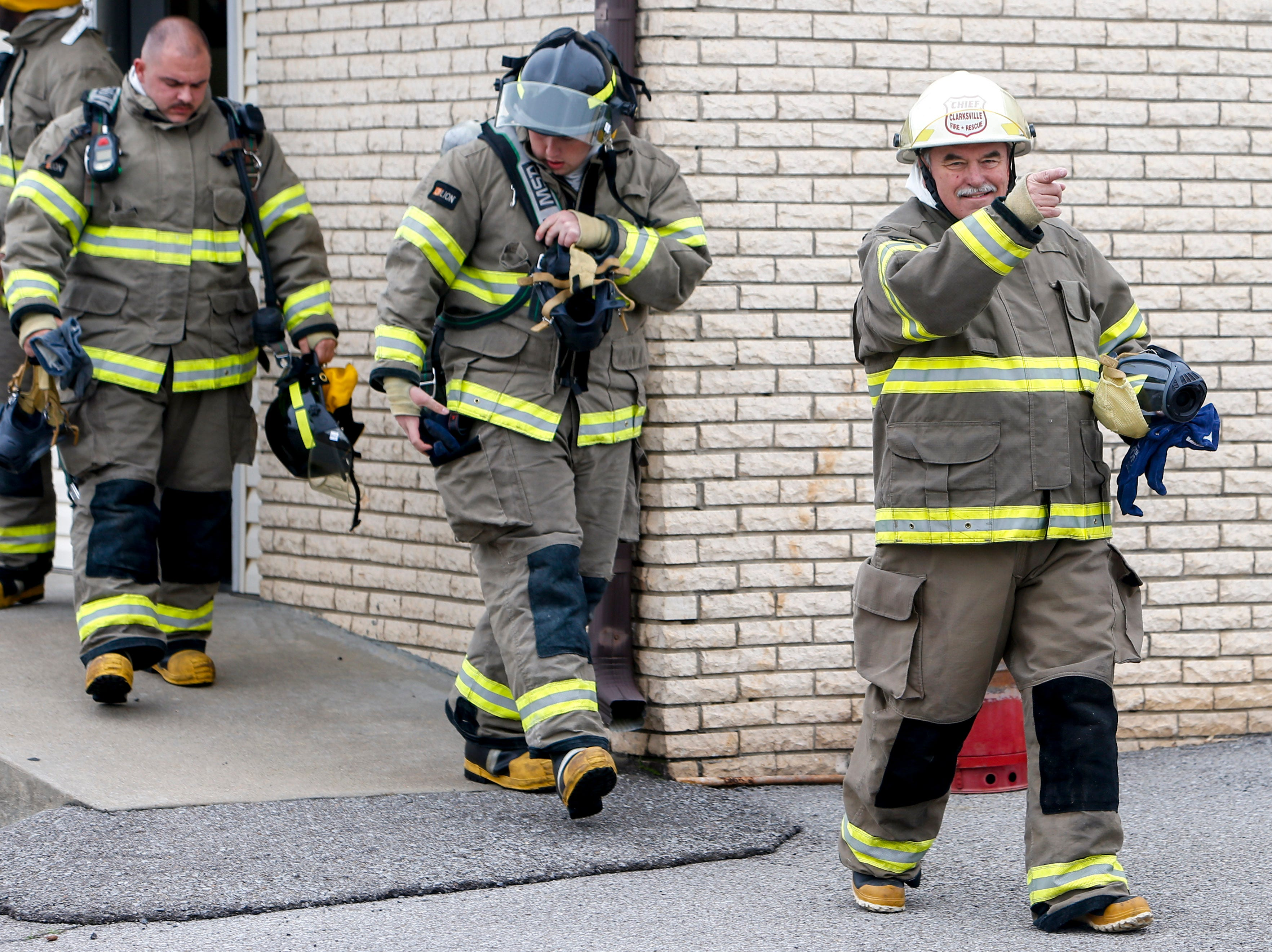 Chief Mike Roberts points to a friend and smiles after emerging from a building in his full uniform at Clarksville Fire Rescue in Clarksville, Tenn., on Friday, May 10, 2019.
