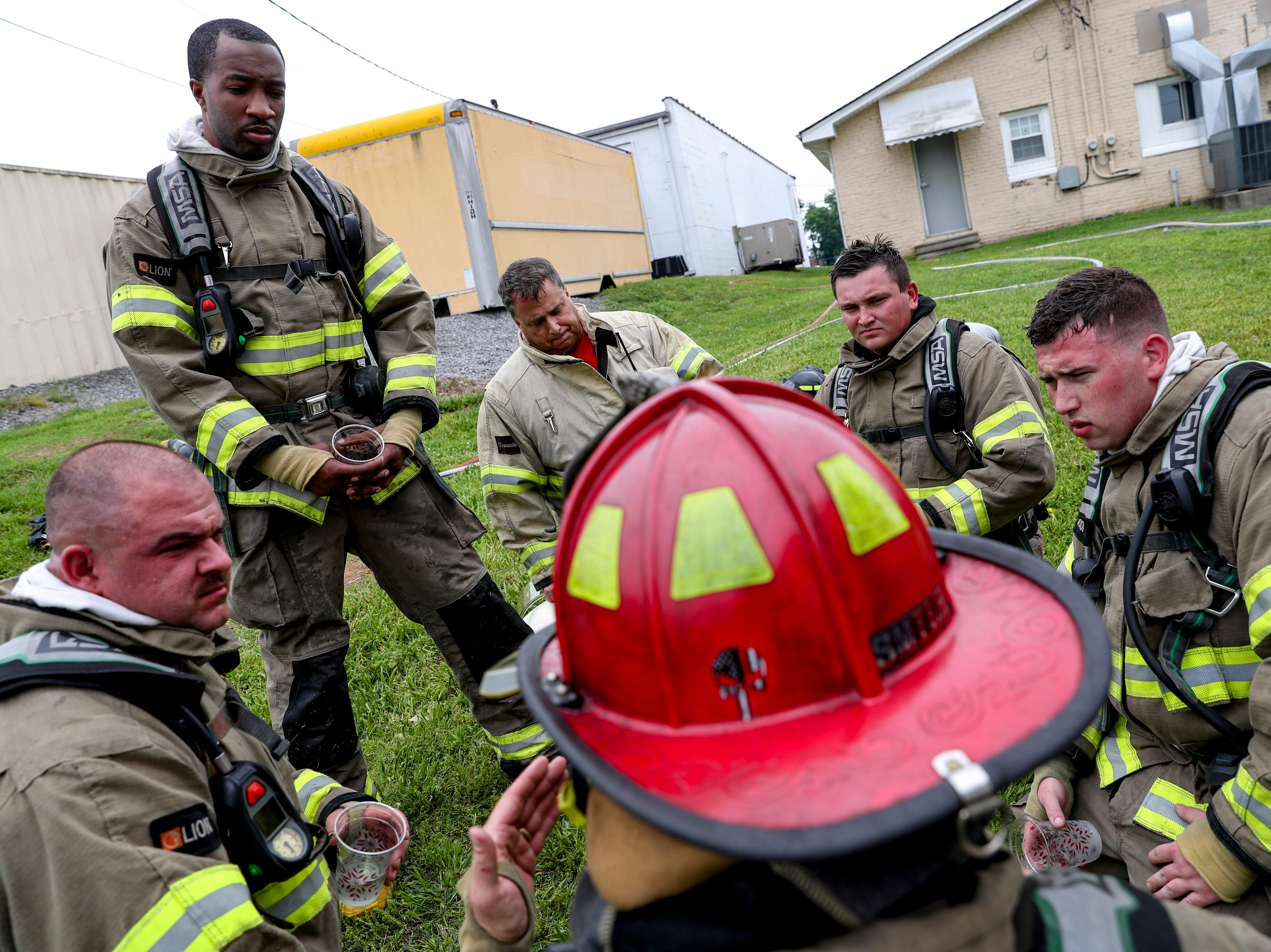 Capt. Butch McCurdy debriefs recruits after an hour working the live fire drill at Clarksville Fire Rescue on Friday, May 10, 2019.