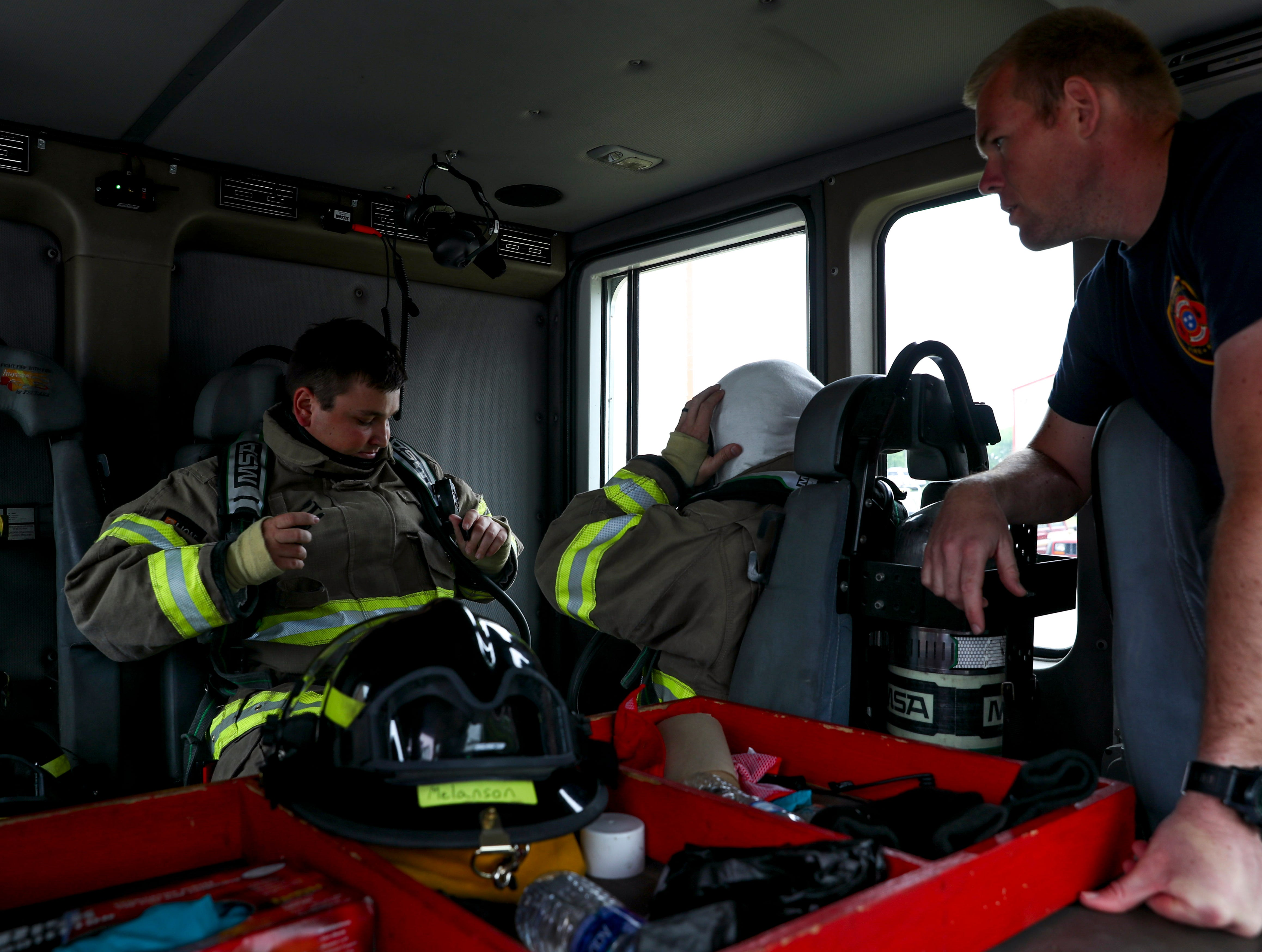 Blake Kiely checks his straps and all his equipment in the engine before riding to the live fire drill at Clarksville Fire Rescue in Clarksville, Tenn., on Friday, May 10, 2019.