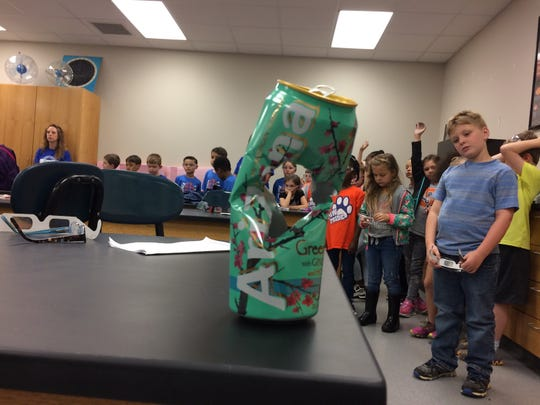 Sango Elementary students listen after a pingpong ball fired by a vacuum cannon pierced an aluminum can.