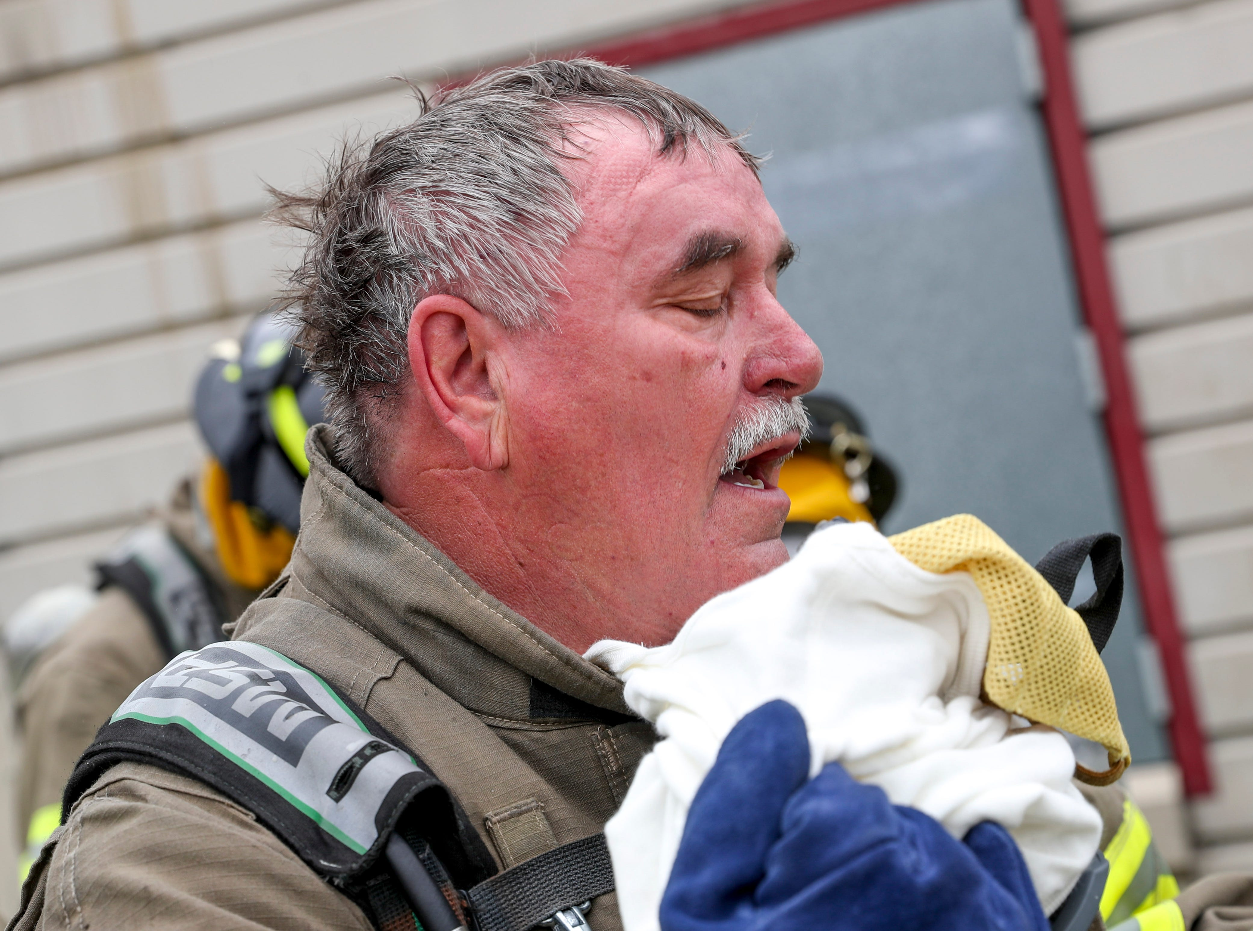 Chief Mike Roberts pulls off his mask and protective layers after emerging fro the burn building at Clarksville Fire Rescue in Clarksville, Tenn., on Friday, May 10, 2019.