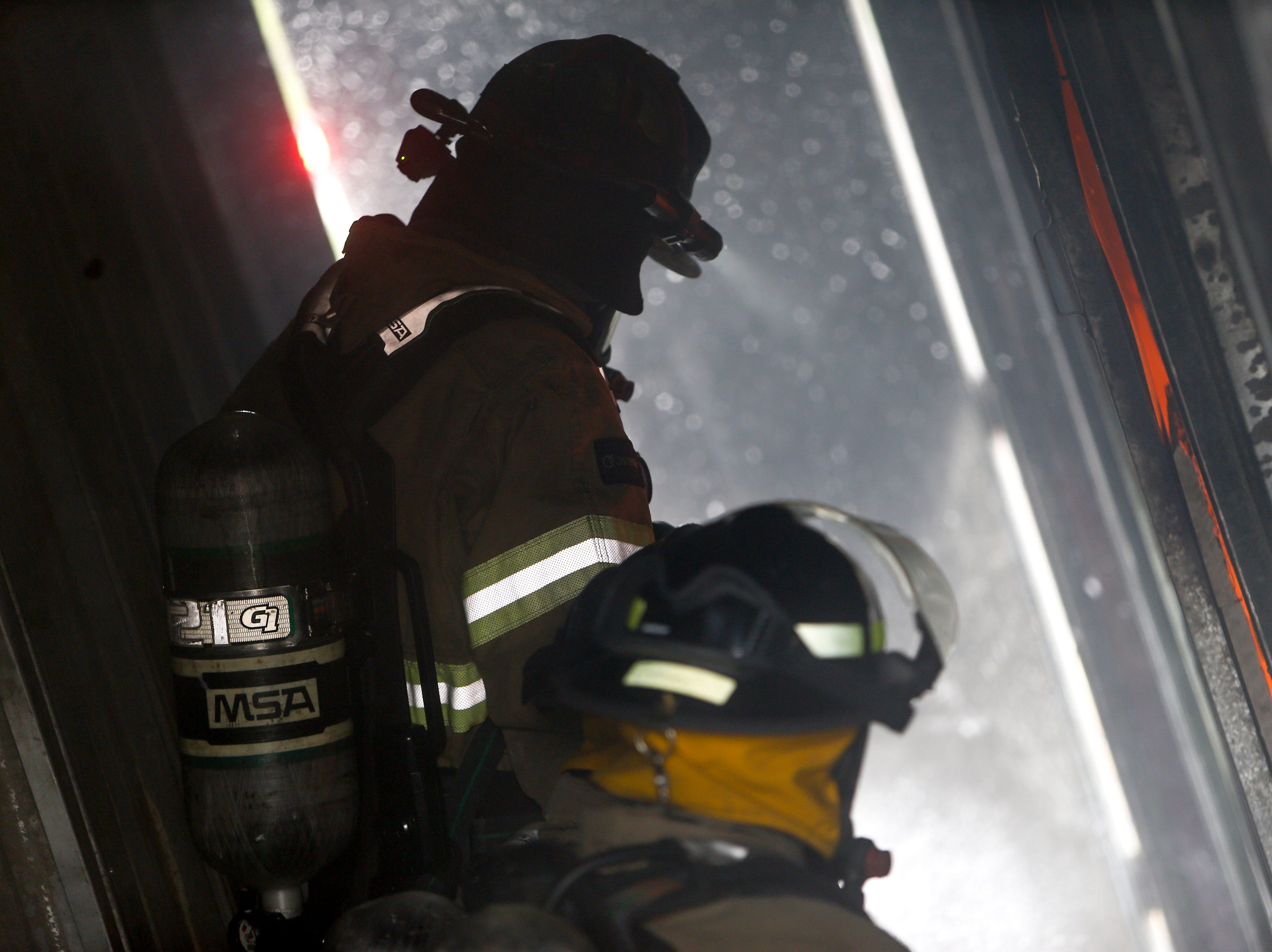 Recruits spray down the insides of a dedicated burn building during a live fire drill at Clarksville Fire Rescue in Clarksville, Tenn., on Friday, May 10, 2019.