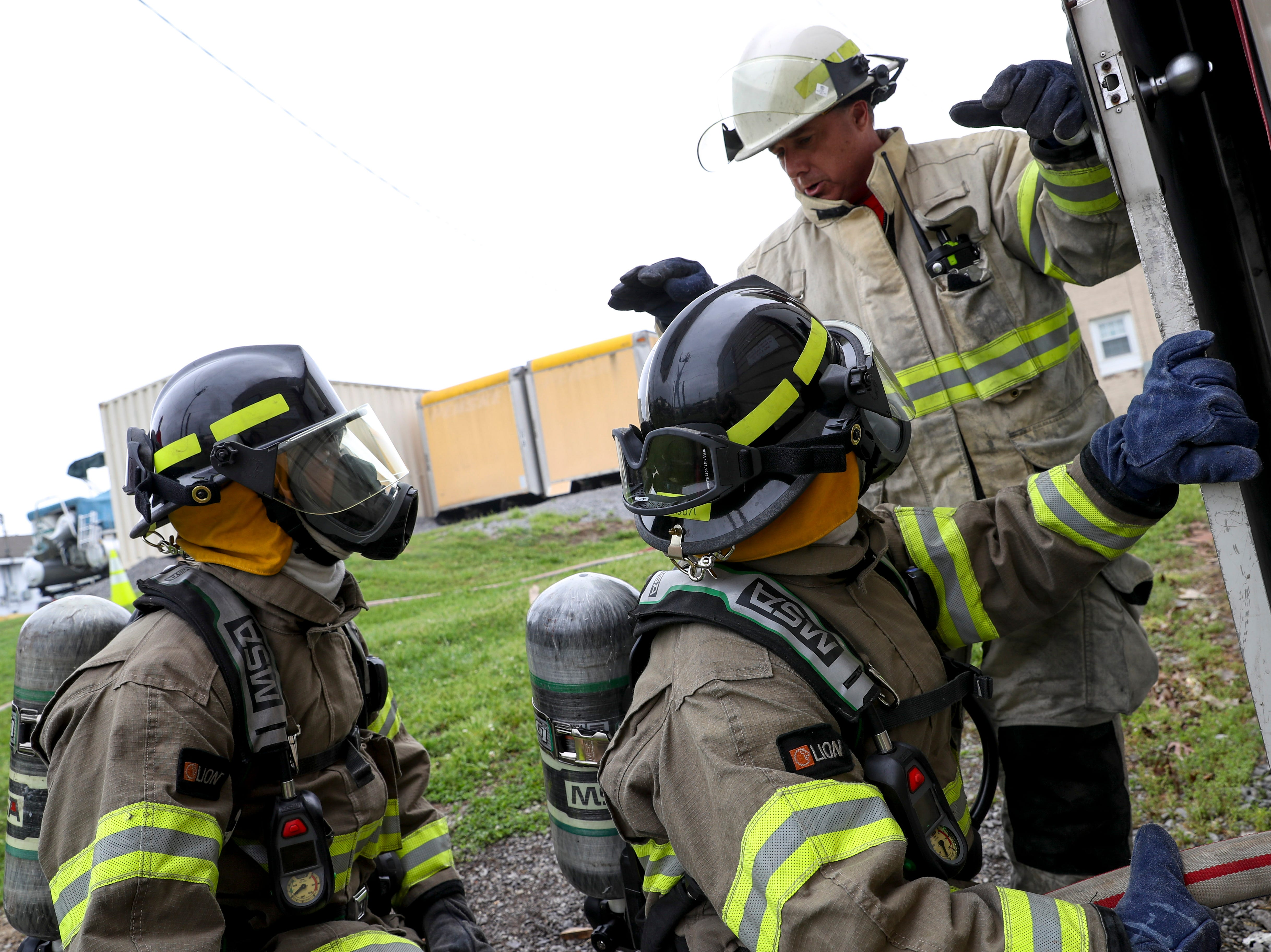 Assistant Chief Randy Ellis instructs new recruits before they head in to the burn building at Clarksville Fire Rescue in Clarksville, Tenn., on Friday, May 10, 2019.
