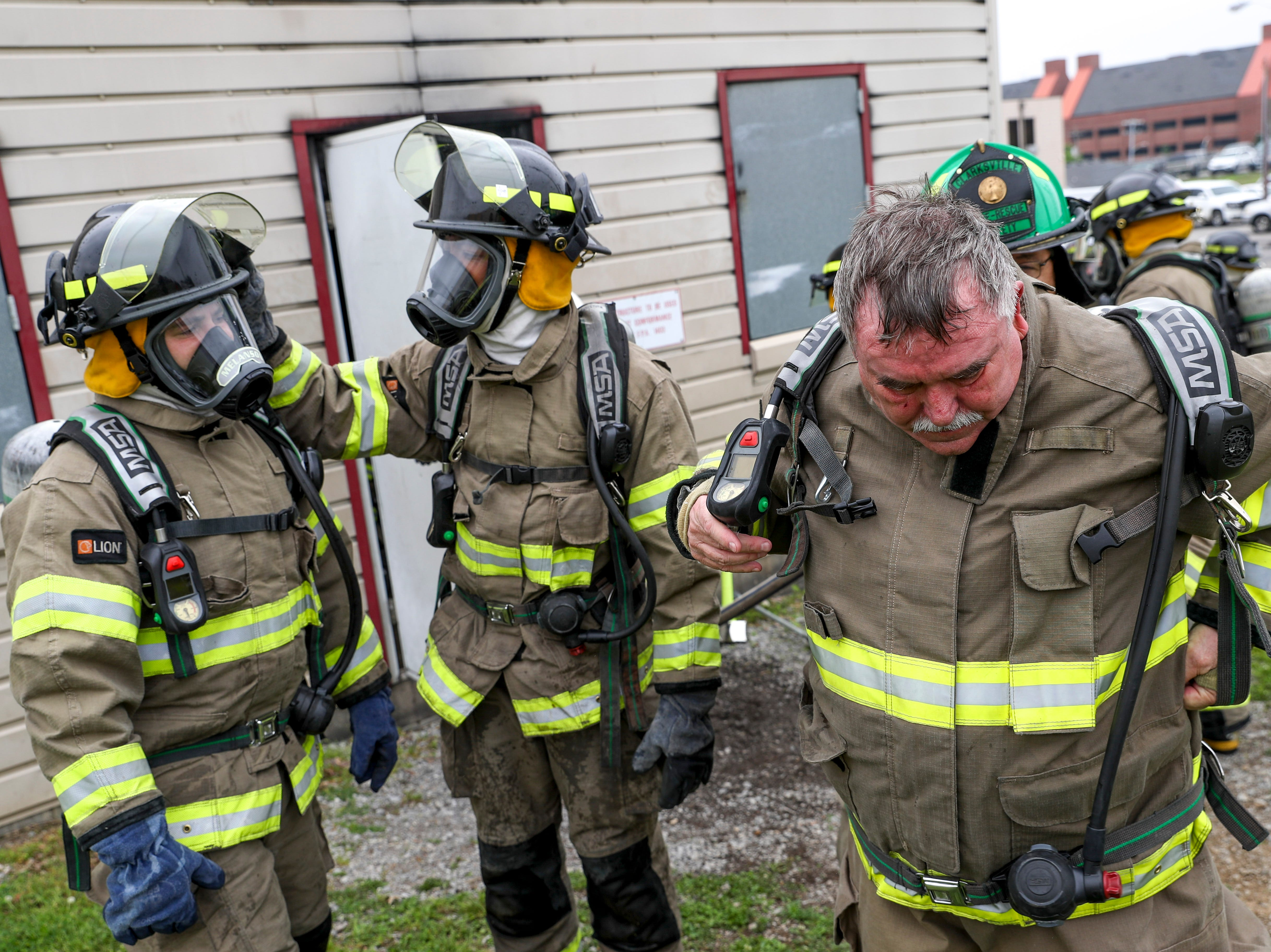 Another firefighter helps remove the oxygen tank from Chief Mike Roberts while new recruits adjust their head gear at Clarksville Fire Rescue in Clarksville, Tenn., on Friday, May 10, 2019.