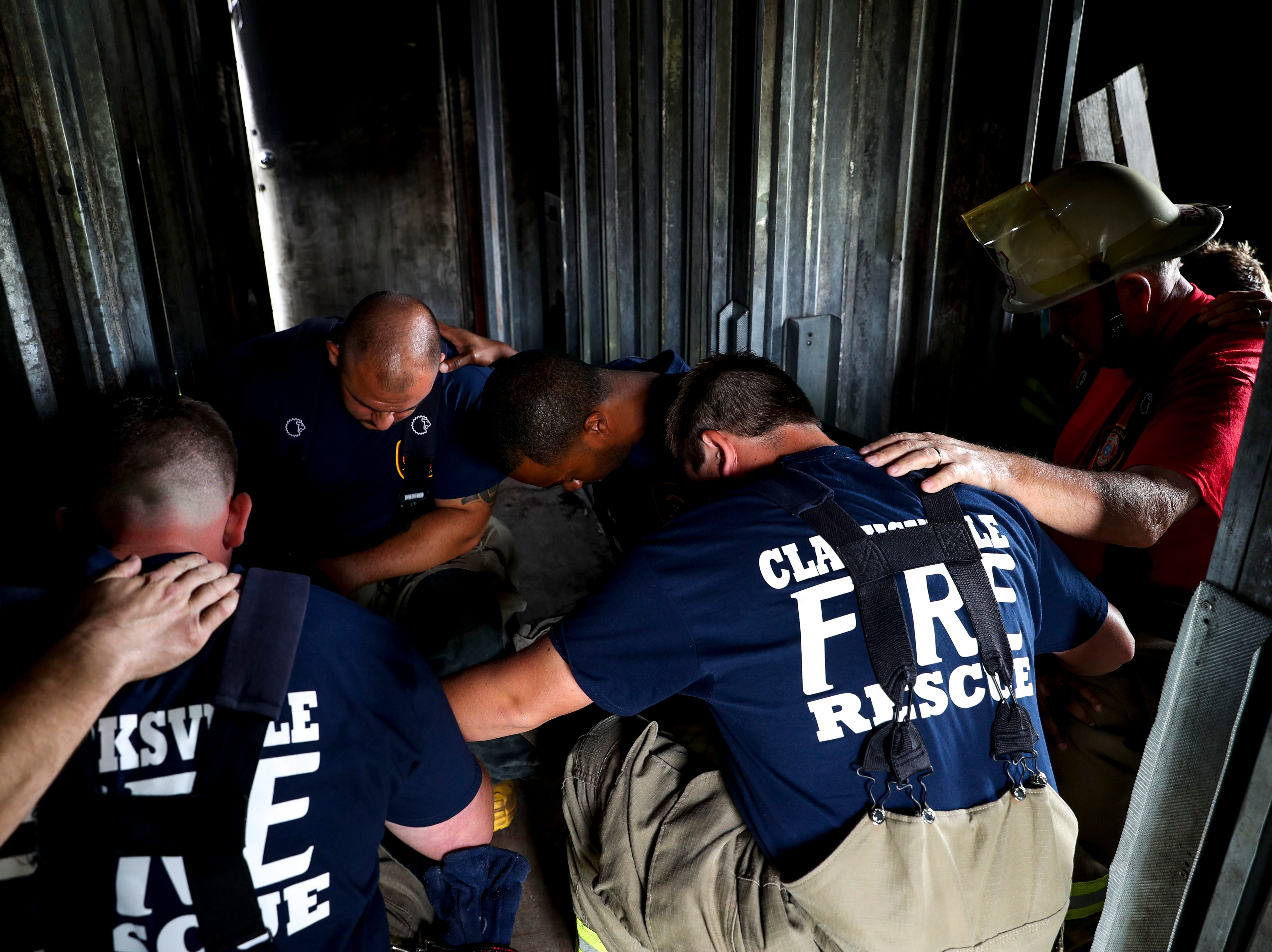 New recruits are joined by Chief Mike Roberts for a prayer inside the burn building before a live fire drill at Clarksville Fire Rescue on Friday, May 10, 2019.