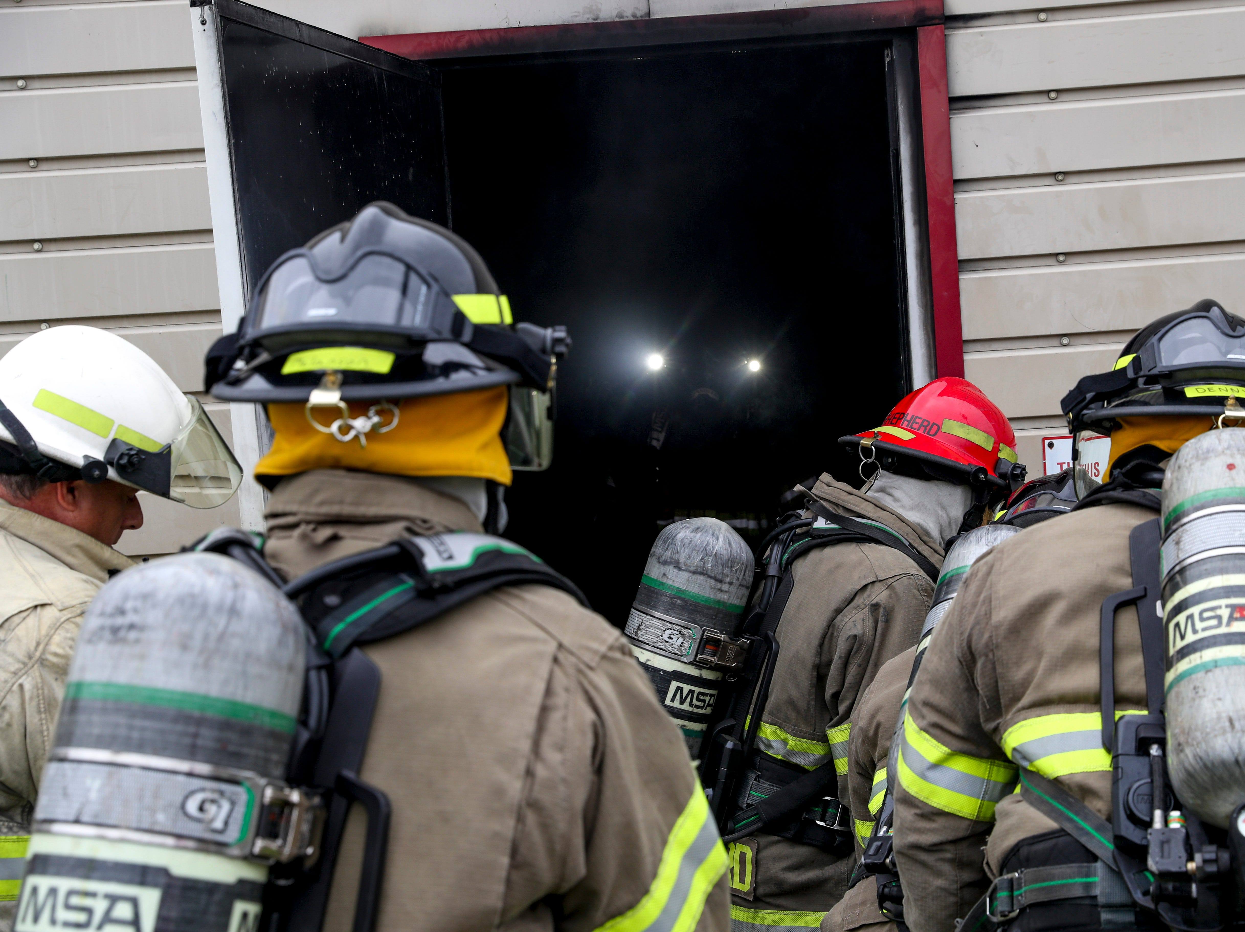 New recruits wait their turn to enter the burn building while the headlights of a Captain are seen approaching them at Clarksville Fire Rescue in Clarksville, Tenn., on Friday, May 10, 2019.