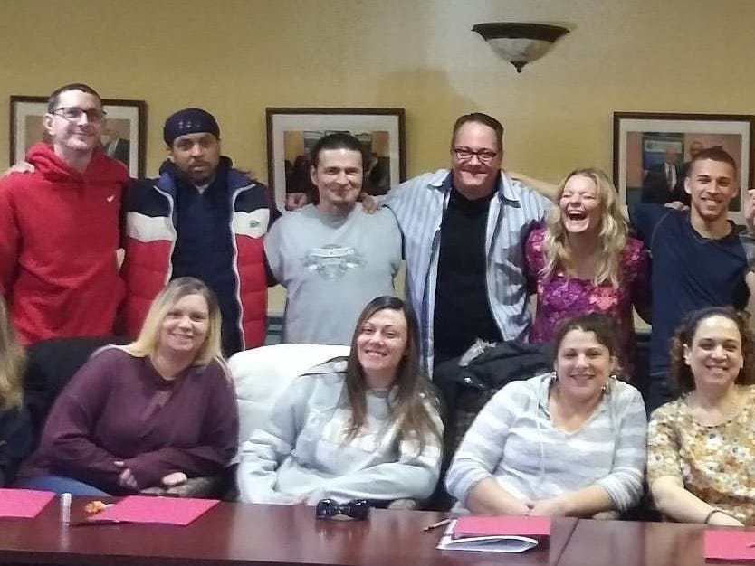 Having lived a life in addiction, Middlesex County's Cheyanne Curtin, 25, (back row, laughing) is now living a life in recovery and is a lead Empowerment Coach with the Linden-based Ammon Foundation.
