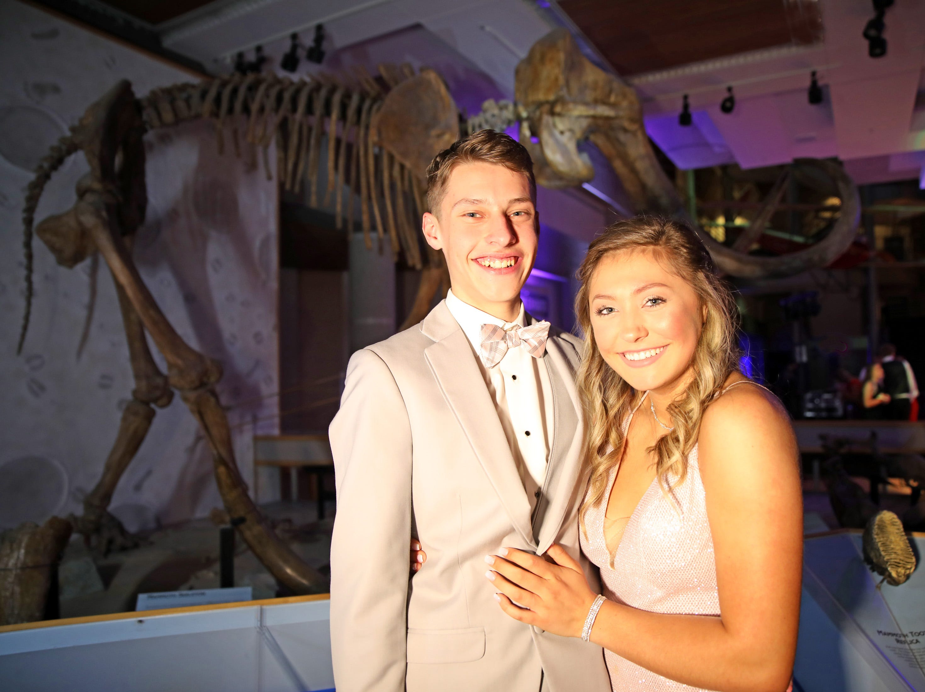 Junior Caden Janek and sophomore Lauryn Maggart stand before the full skeleton replica of a Hebior mammoth during the circus-themed Urbandale High School Junior/Senior Prom Spectacular at the State Historical Building in Des Moines on Saturday, April 11, 2019.  The post-prom event is held at school right after the dance from 11 p.m. to 4:30 a.m. with food, prizes, a hypnotist, inflatables, and casino games.
