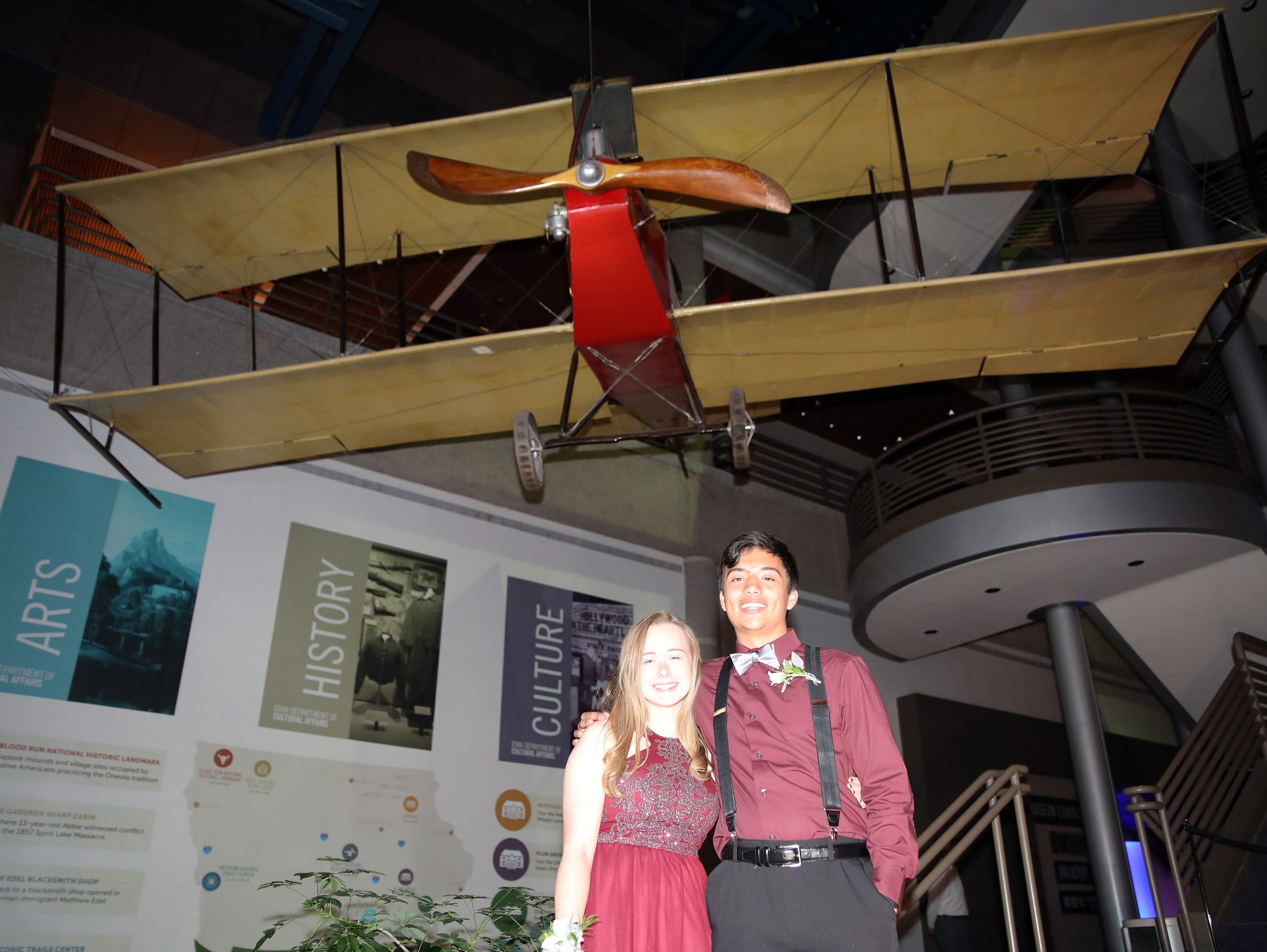 Sophomore Madison Fett and senior Alexander Correa stand below the Oscar Solbrig Benoist Tractor Biplane during the circus-themed Urbandale High School Junior/Senior Prom Spectacular at the State Historical Building in Des Moines on Saturday, April 11, 2019.  The post-prom event is held at school right after the dance from 11 p.m. to 4:30 a.m. with food, prizes, a hypnotist, inflatables, and casino games.