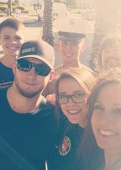 (Back row, left to right) Tristin Laue, his brother and dad Braden and Mitch Laue, smile with (front row, left to right) Alex Luke, his girlfriend Madison Stoffregen, and her mom and Tristin's and Braden's stepmom Debbie Nichols, at Braden's graduation from U.S. Marines boot camp in San Diego.