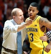 Michigan head coach John Beilein talks to Trey Burke (3) during the second half of their NCAA college basketball game against Illinois, Sunday, Jan. 27, 2013, in Champaign, Ill. Michigan won 74-60.
