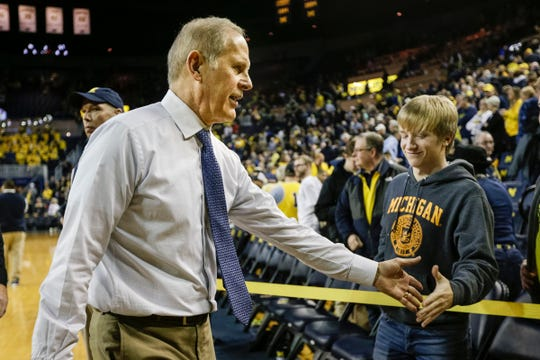 John Beilein shakes hands with a fan, after a win last season at Crisler Center in Ann Arbor.